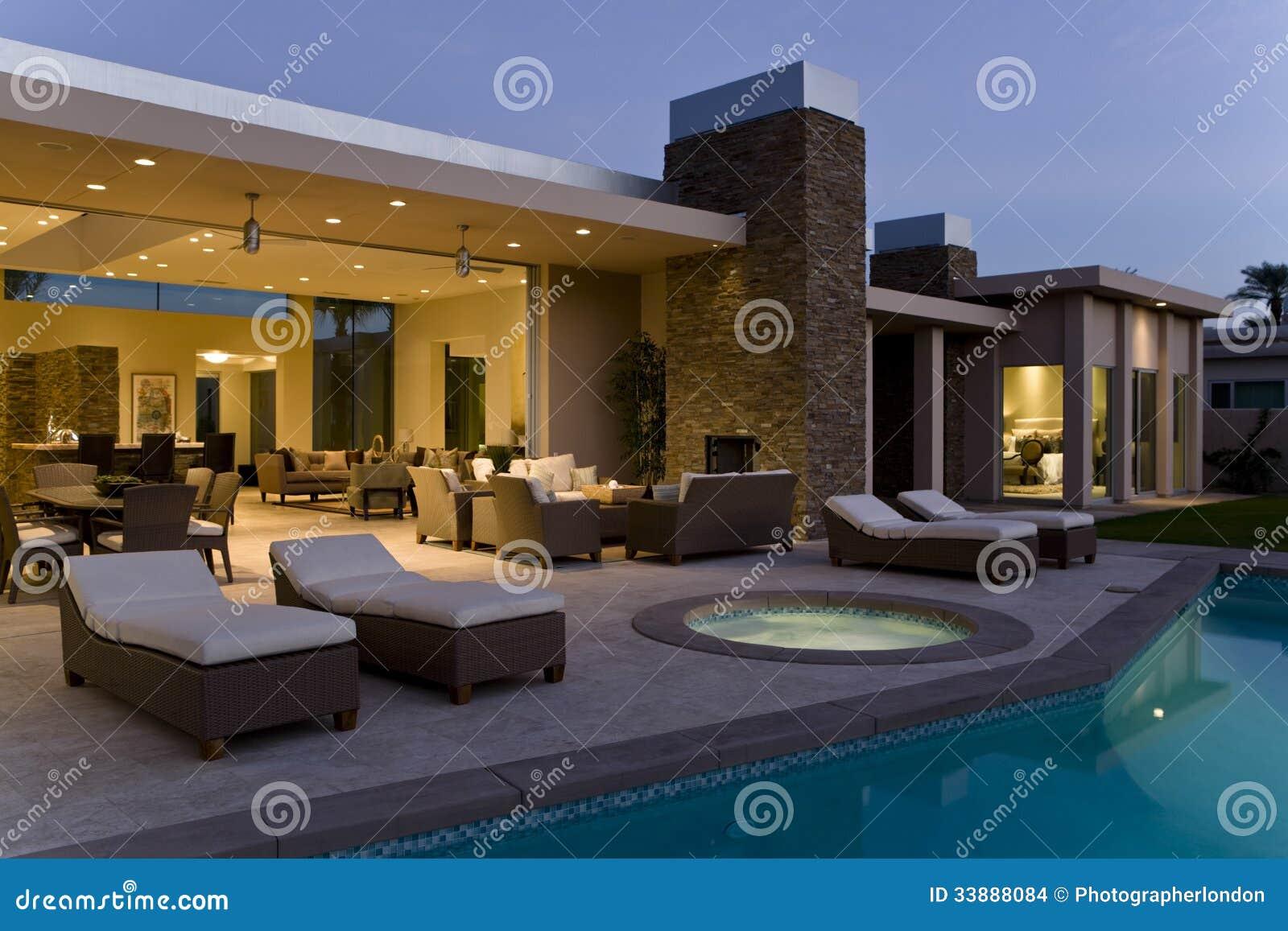Camera con Sunloungers sul patio dallo stagno al crepuscolo