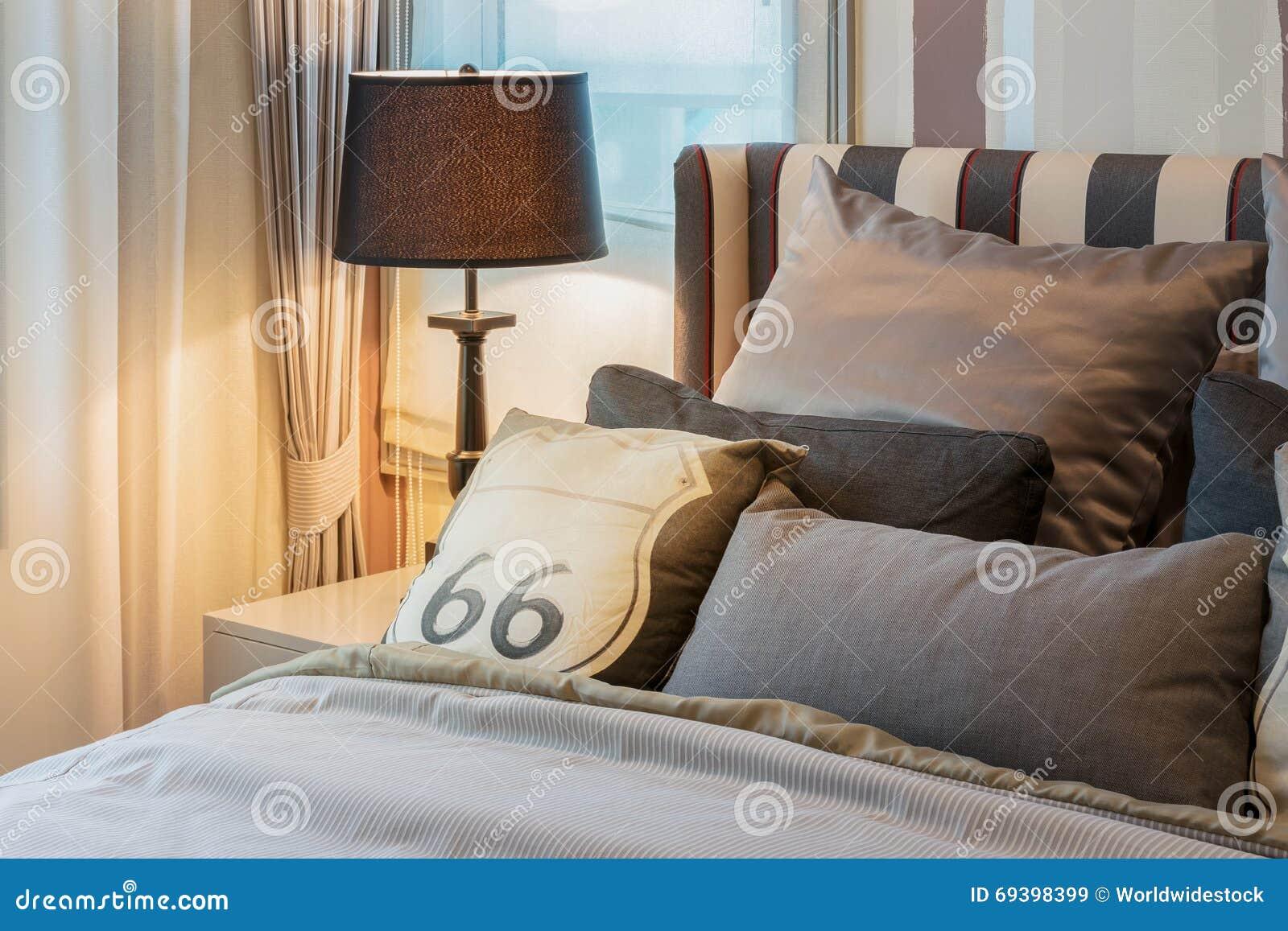 Camera da letto accogliente con i cuscini di marrone scuro e la lampada di lettura immagine - Letto con cuscini ...