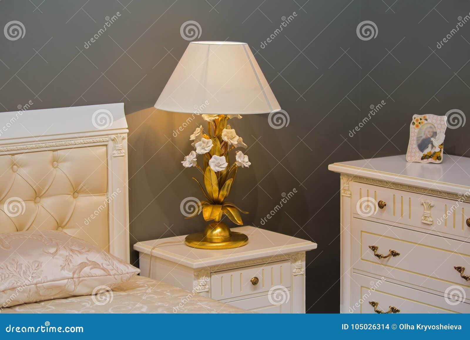 Camera da letto bianca reale di lusso nello stile antico comodino