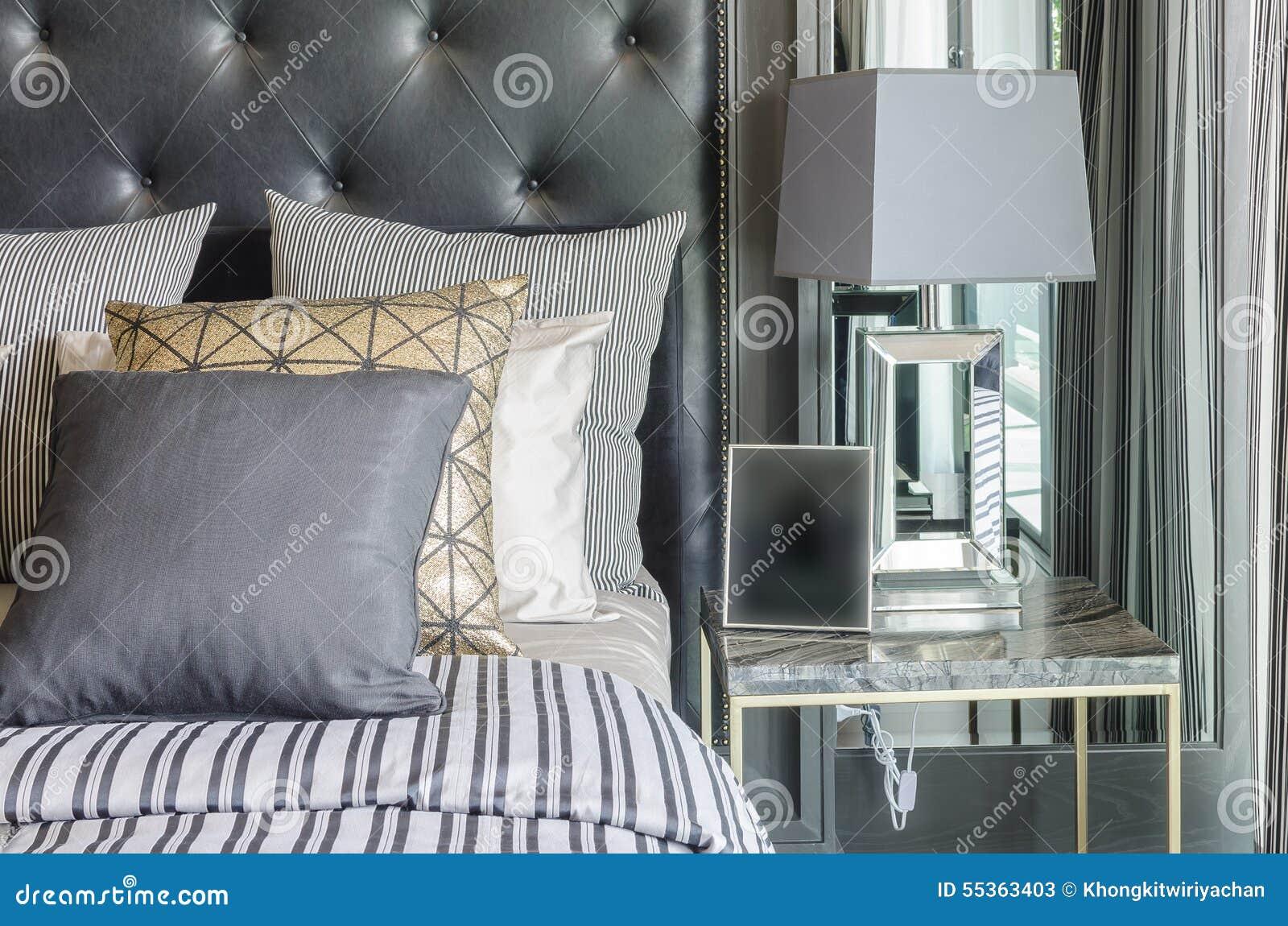 Camera da letto in bianco e nero di lusso con la lampada grigia sulla tavola