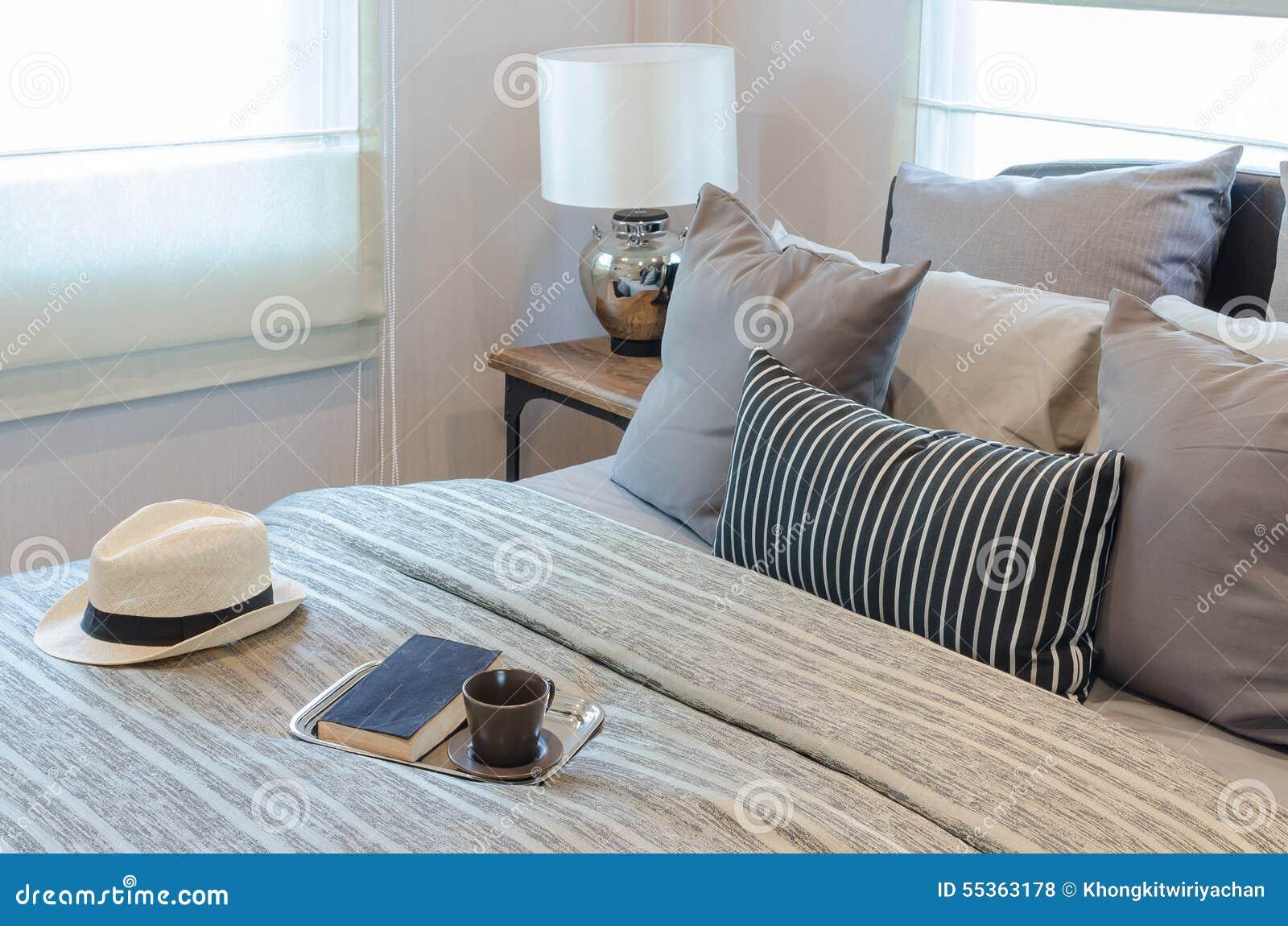 Camera da letto classica di stile con il cappello ed il vassoio di libro con la tazza