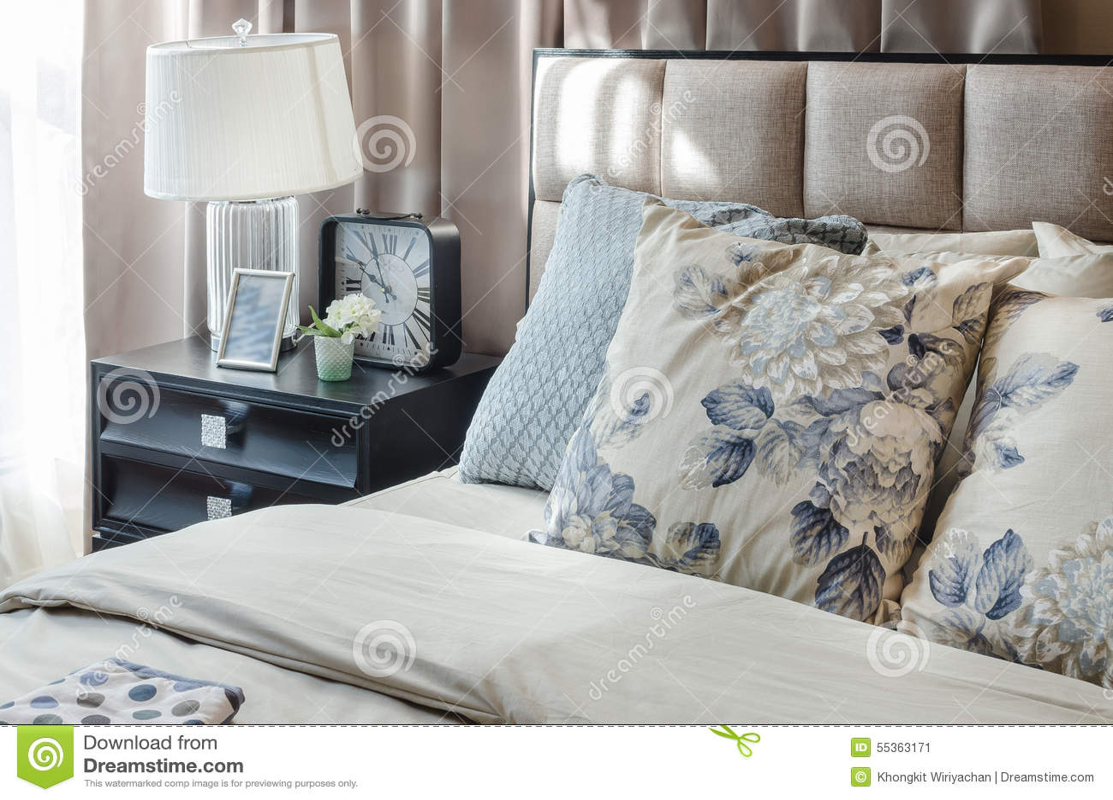 Camera da letto di lusso con la lampada e la sveglia sulla tavola di legno