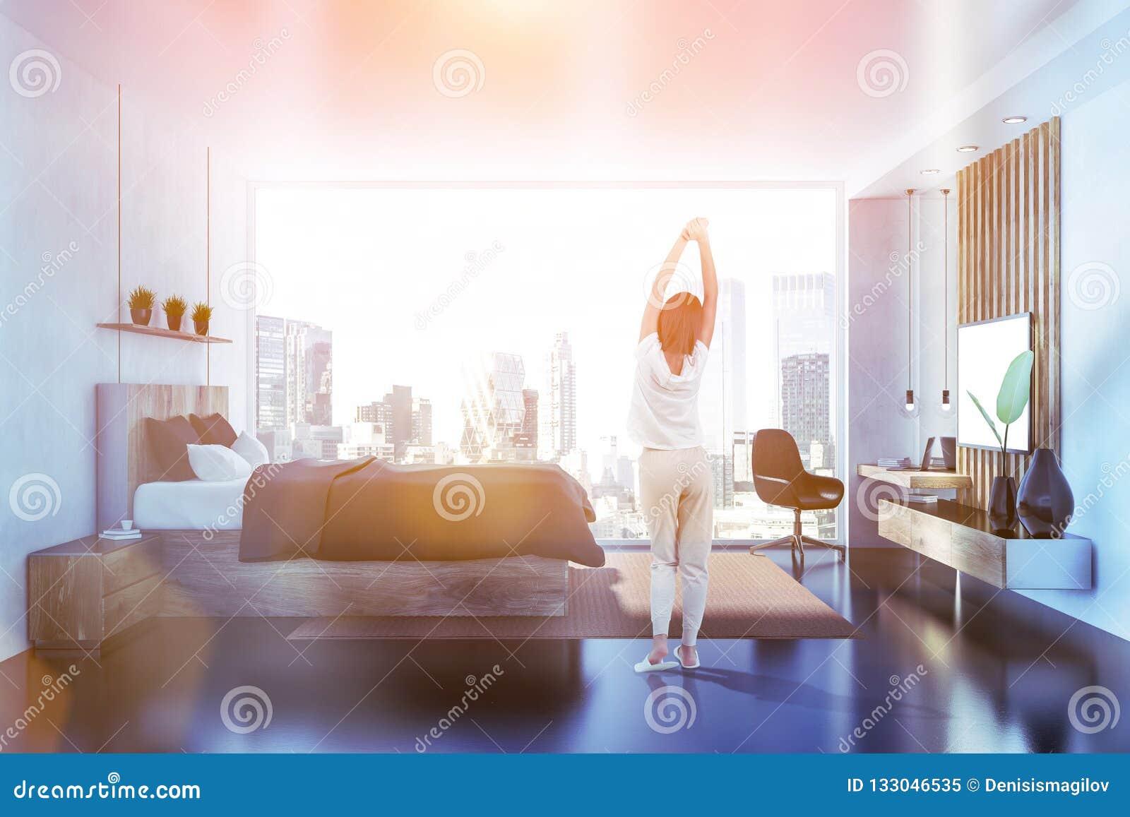 Camera da letto grigia con la vista laterale della TV, donna