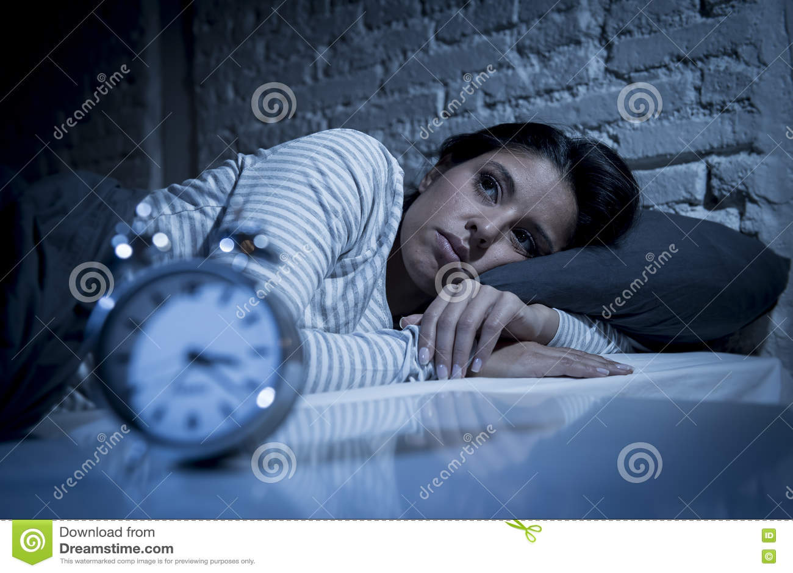 Camera da letto ispana della donna a casa che si trova a letto tardi alla notte che prova a dormire insonnia di sofferenza