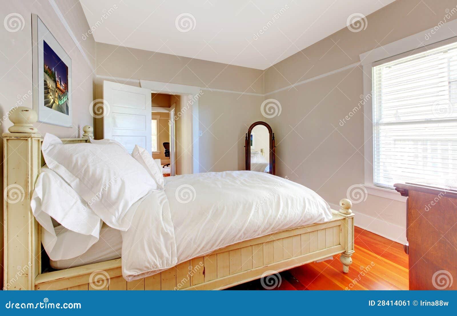 ... Stock: Camera da letto luminosa con il letto bianco e le pareti beige
