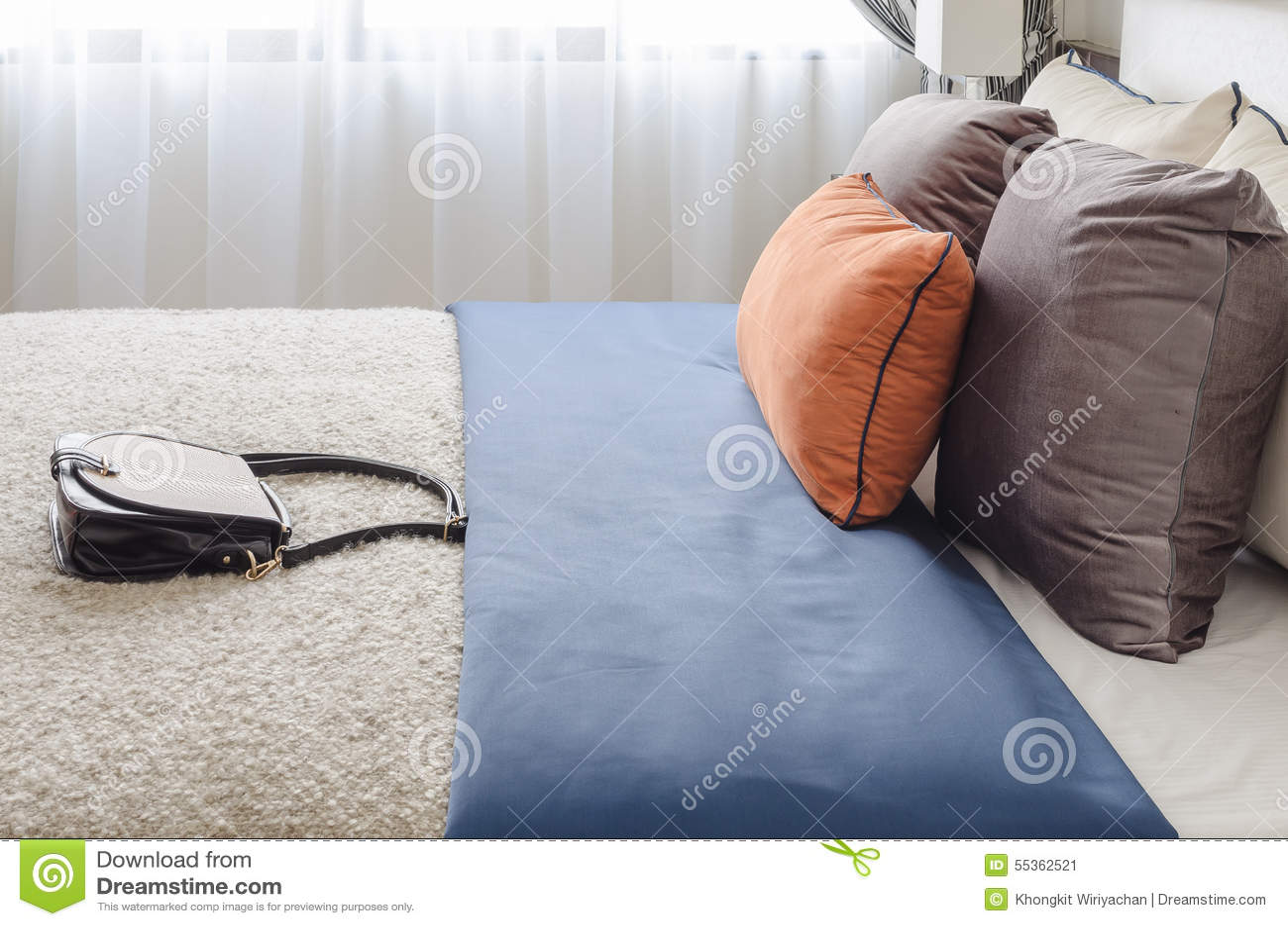 Camera da letto moderna con i cuscini variopinti e la borsa della femmina