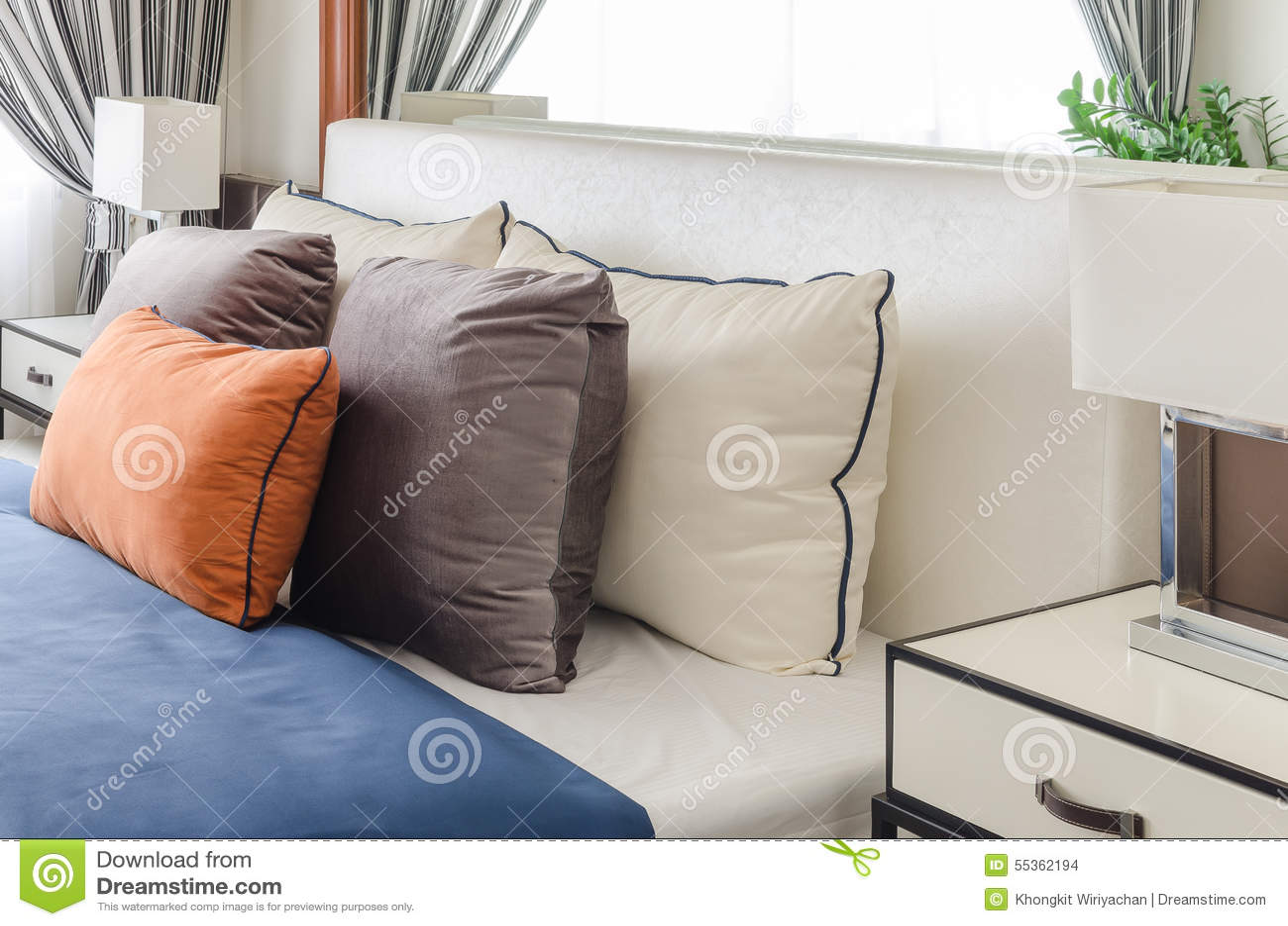 Camera da letto moderna con il cuscino arancio e la coperta blu