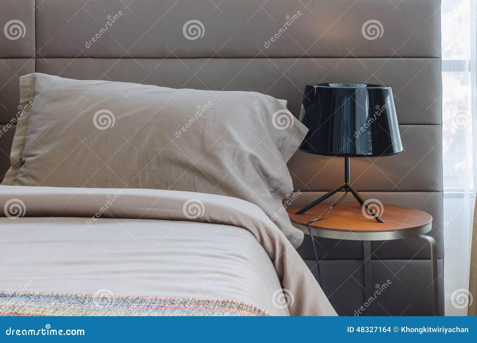 Camera da letto moderna con la lampada nera sulla tavola di legno