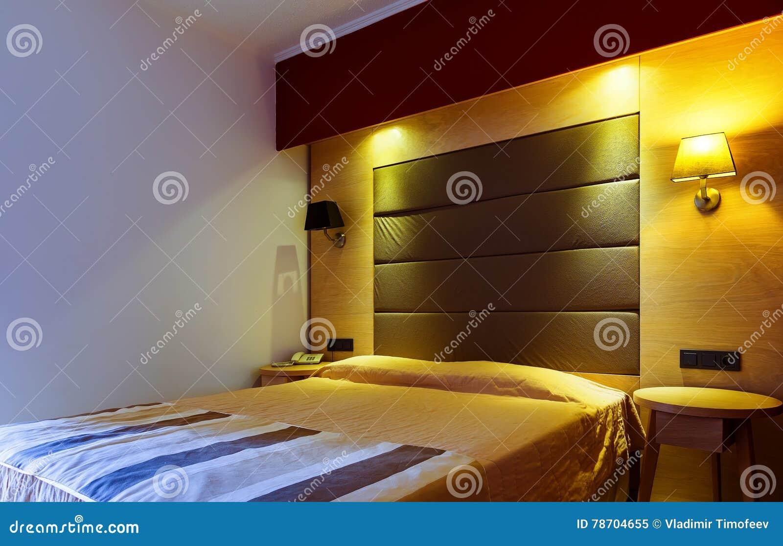 Camera da letto o camera di albergo moderna, calda, d invito Luce ed ombre