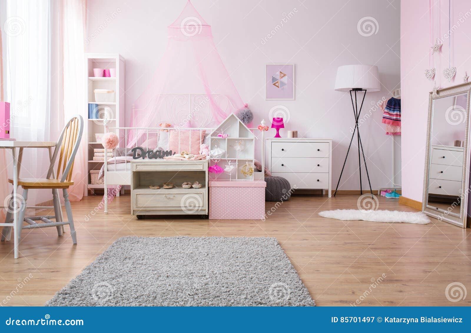 Camera da letto spaziosa della ragazza nel rosa immagine stock