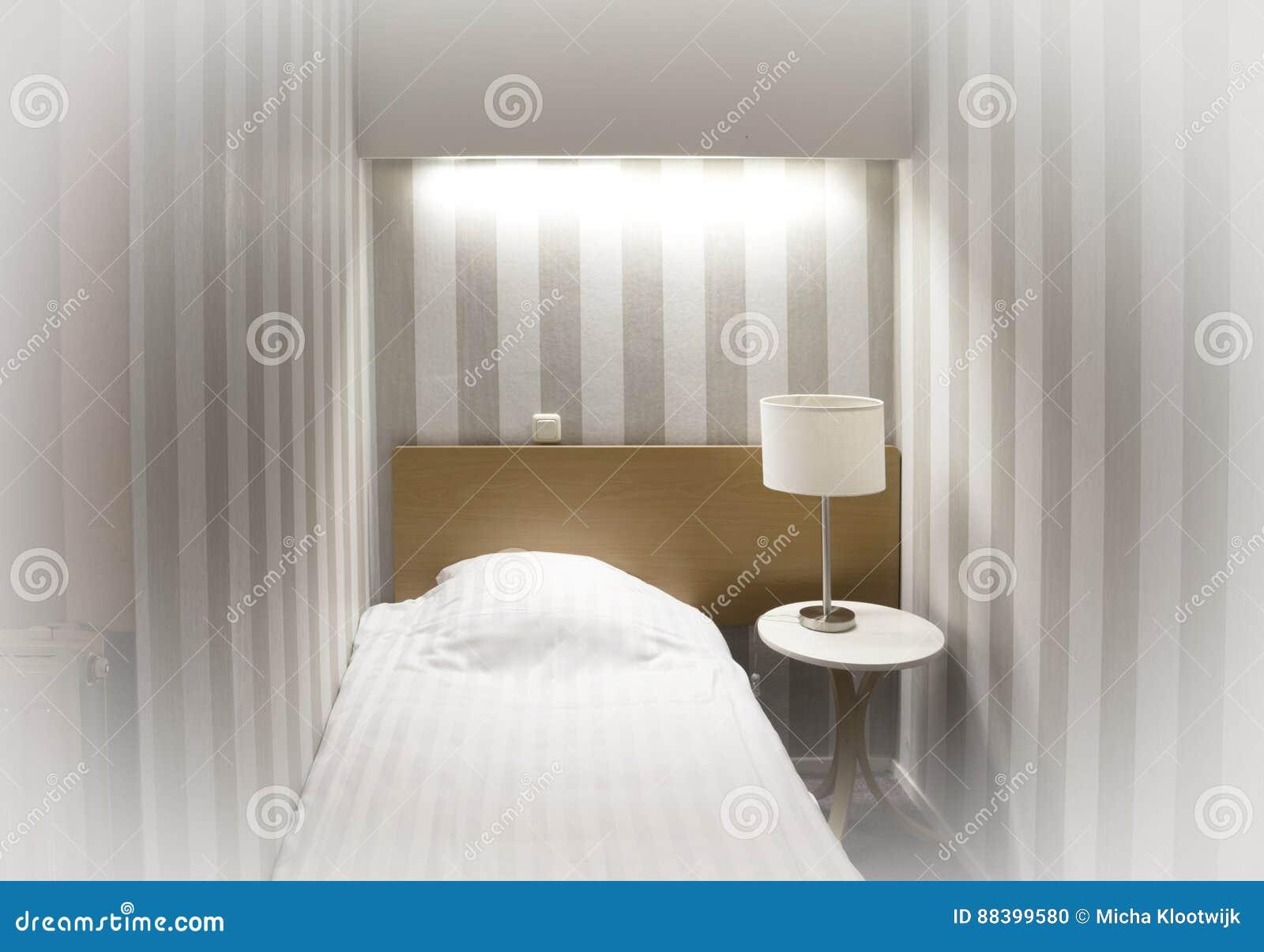 Camera di albergo semplice letto singolo fotografia stock