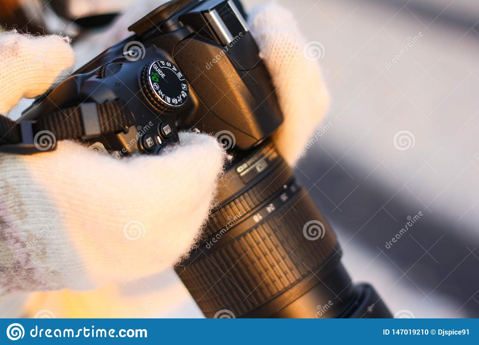 Camera in the hands of a girl in the winter forest