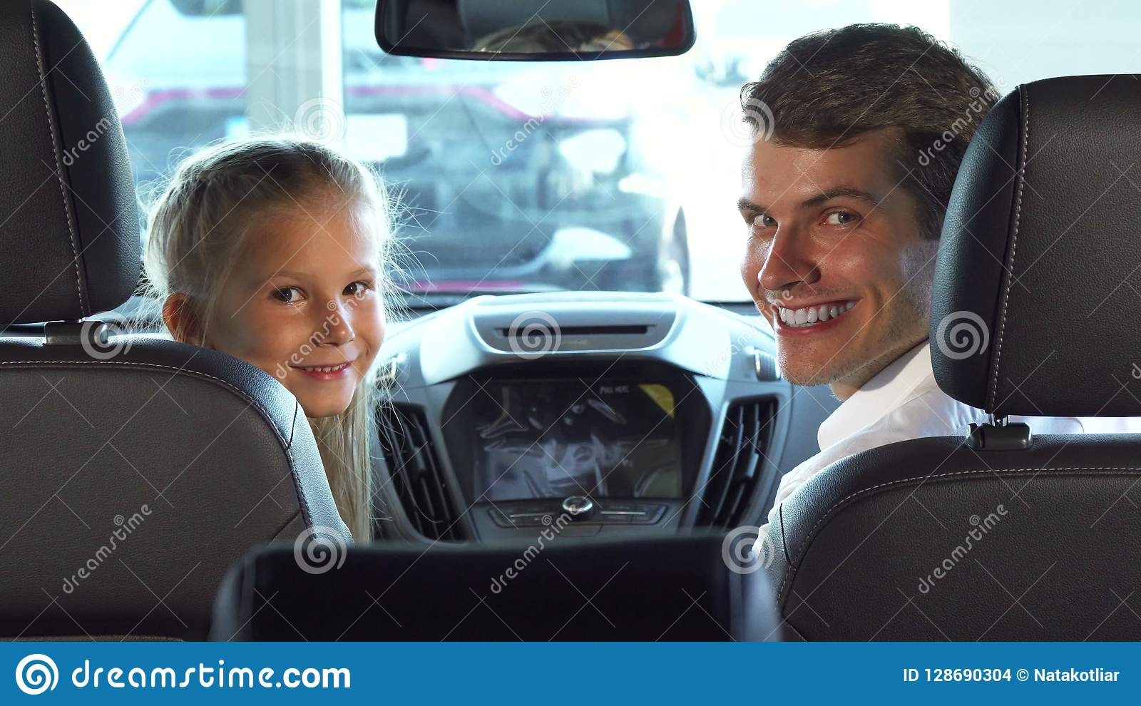 Funny Dad With His Daughter Sit In The Front Seats And Look At The