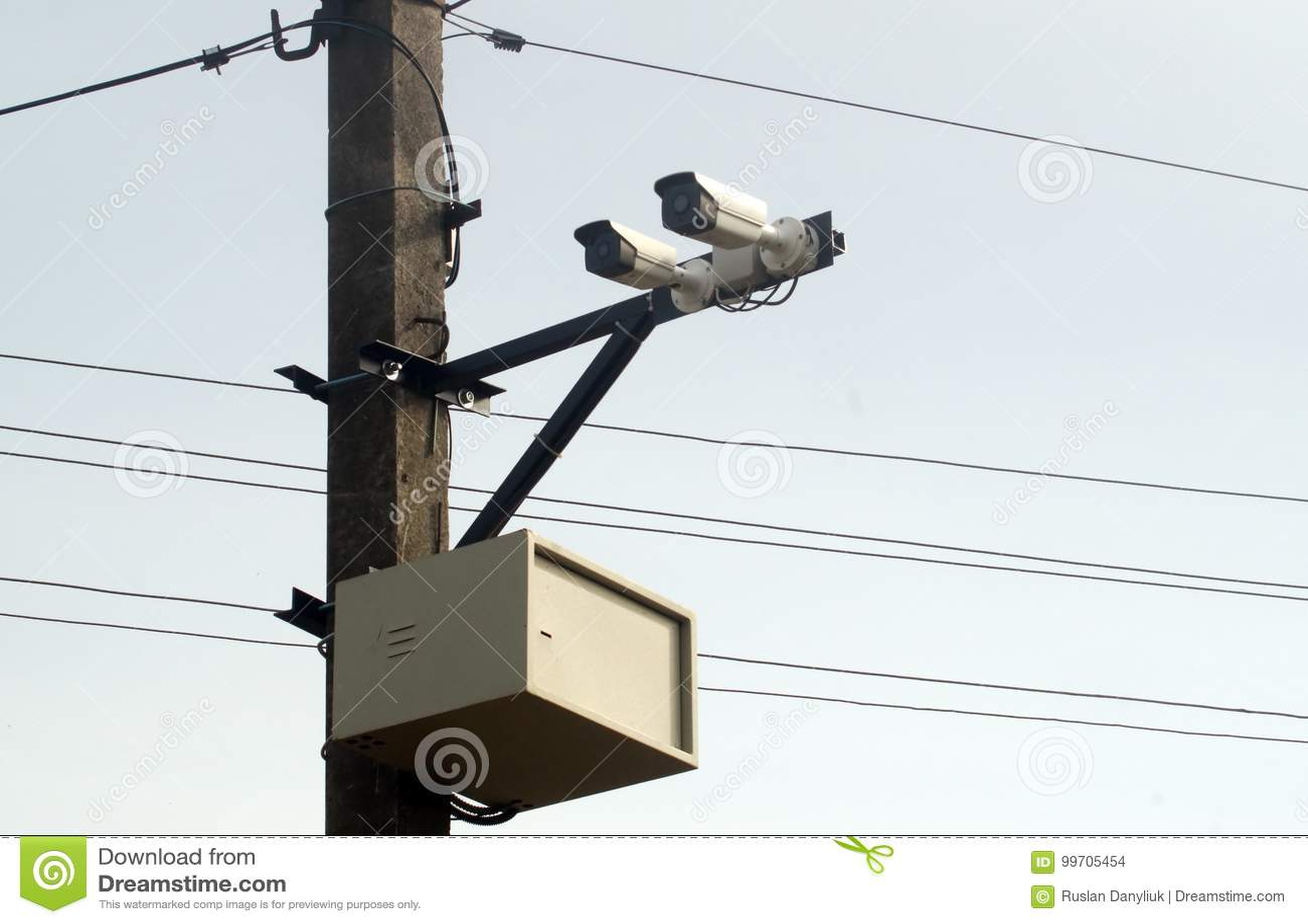 Camera surveillance on pillar near road for traffic monitoring.