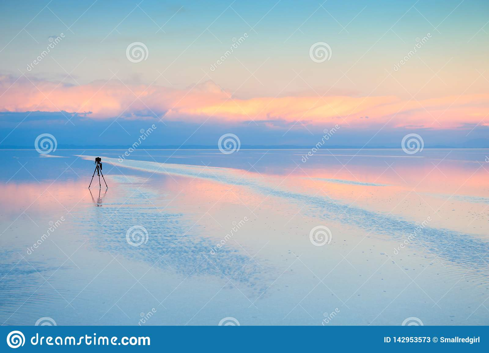 Camera with tripod shooting sunset on Salar De Uyuni salt flat in Bolivia