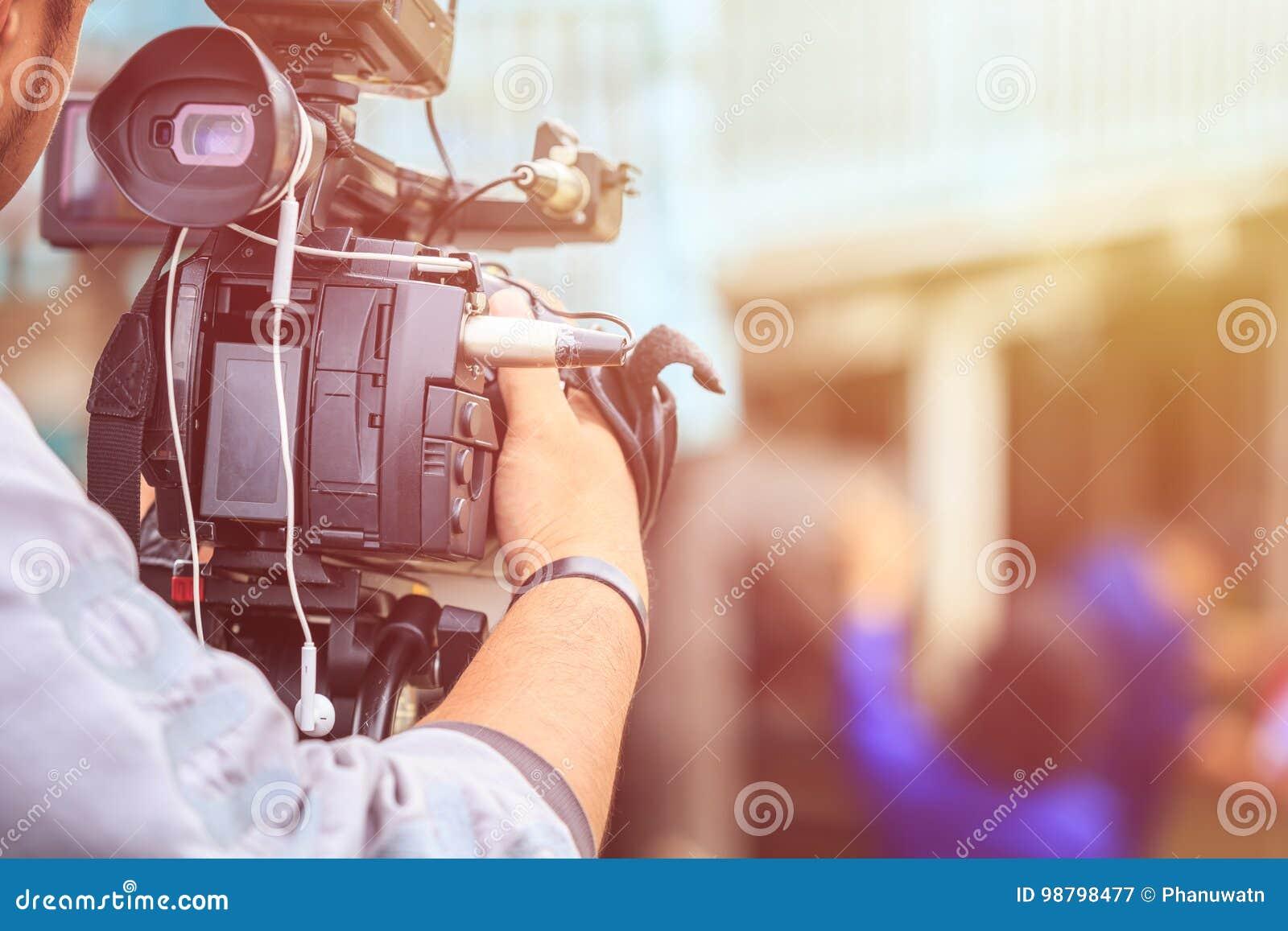 Cameraman que usa la cámara de vídeo digital profesional Disposición al aire libre