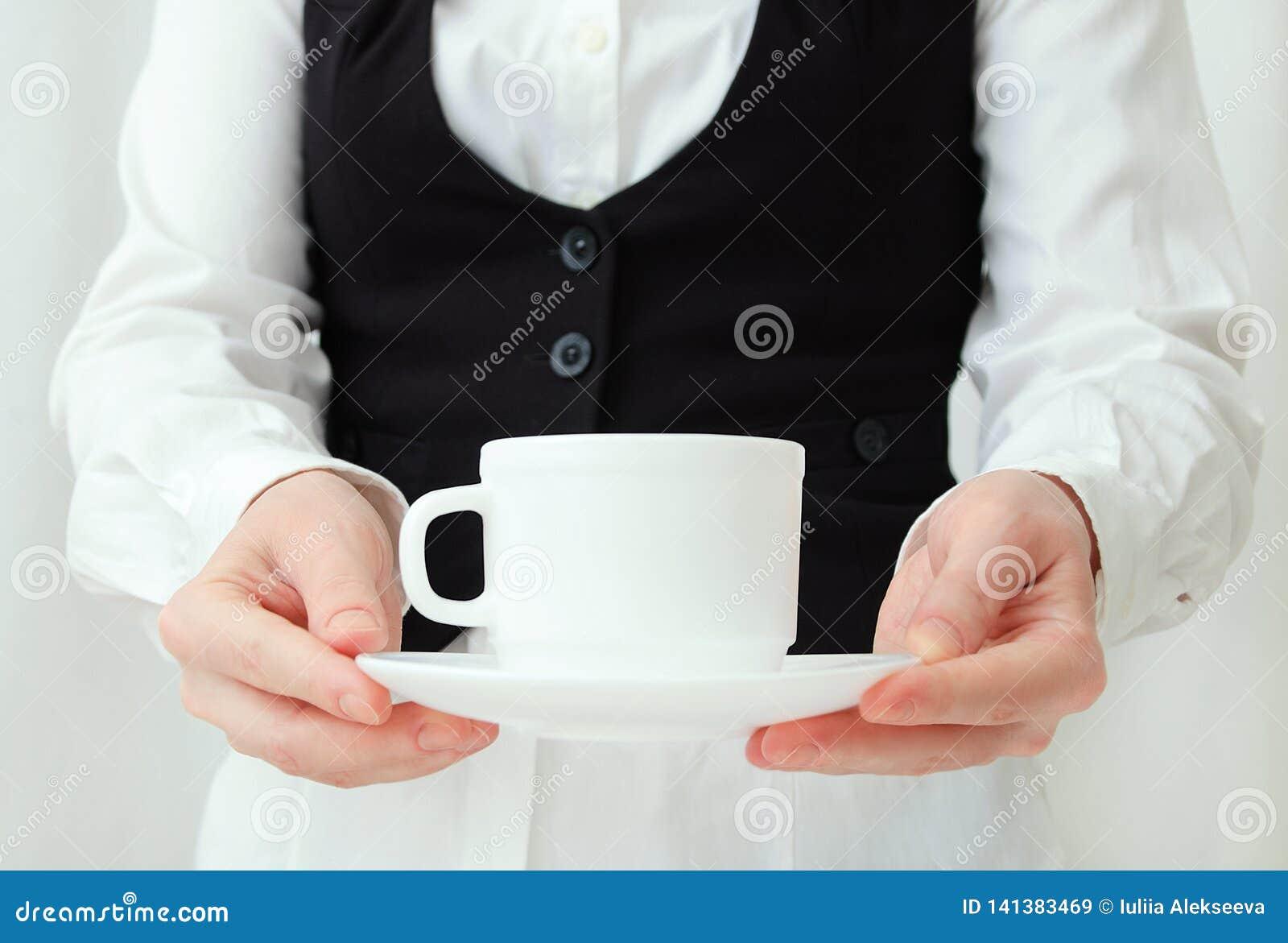 Cameriere caucasico della ragazza in camicia bianca e maglia nera con le paia del tè in mani