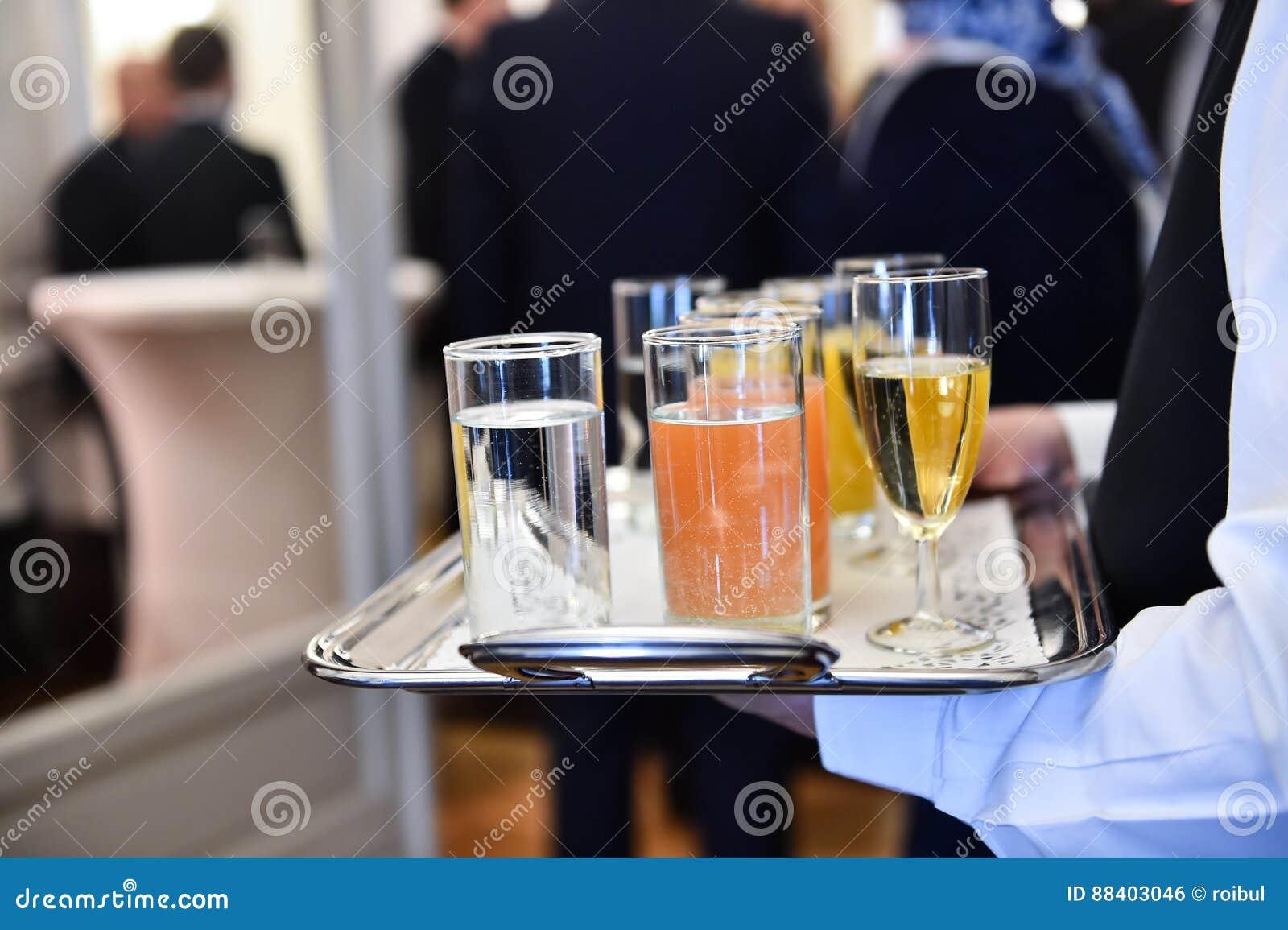 Cameriere che tiene un vassoio con le bevande durante il ricevimento pomeridiano