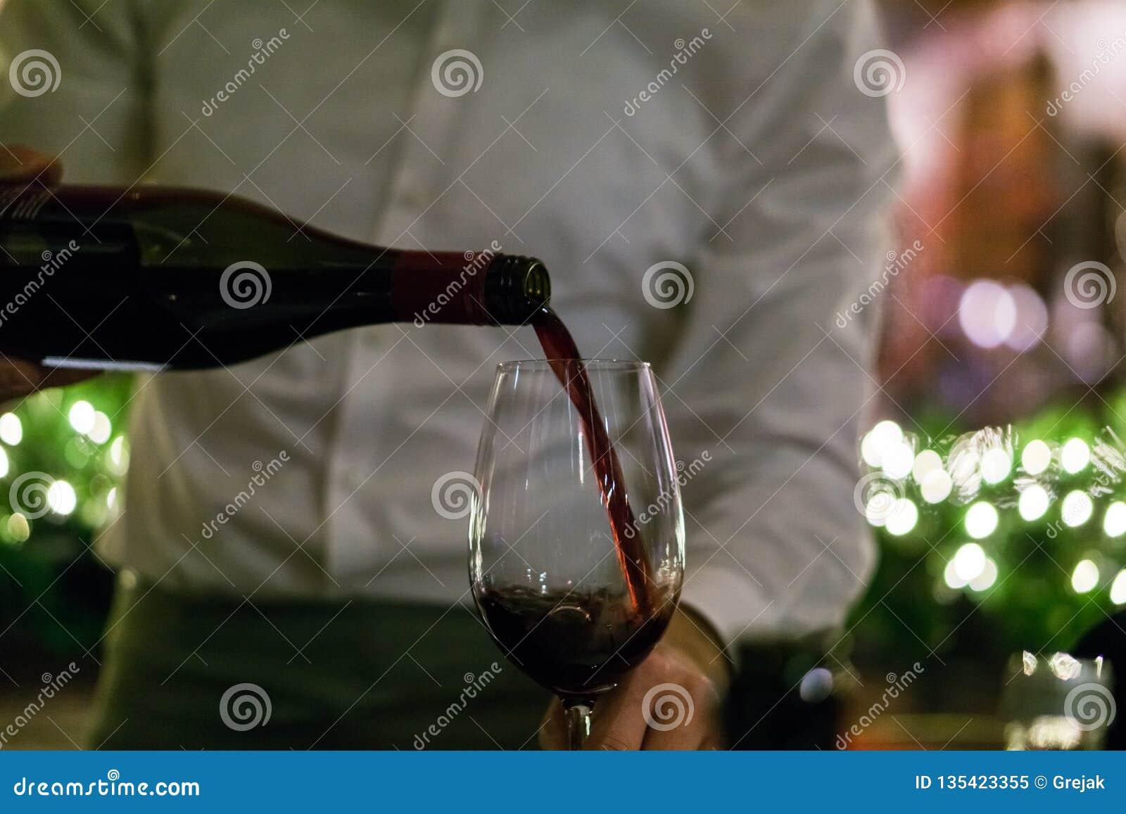 Cameriere che versa vino rosso in un vetro