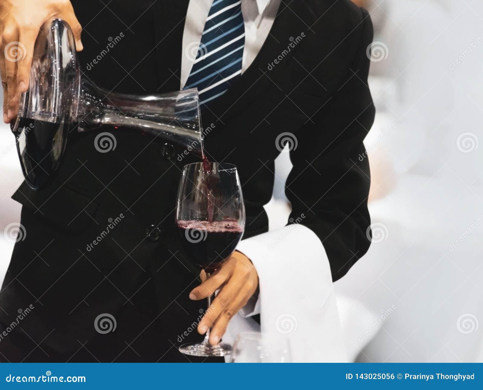 Cameriere che versa vino rosso in un vetro ad una tavola del ristorante