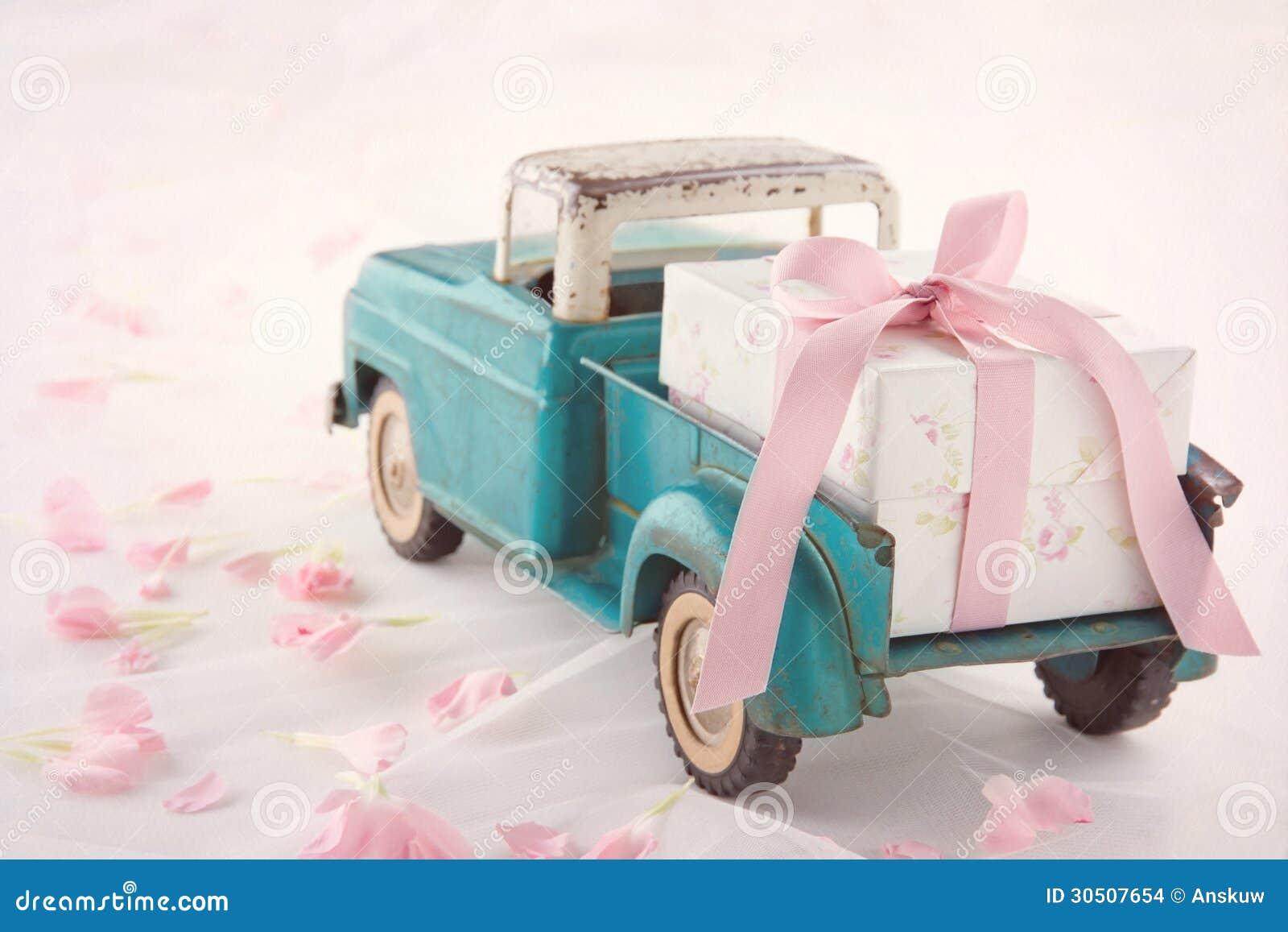 Camión antiguo del juguete que lleva una caja de regalo con la cinta rosada