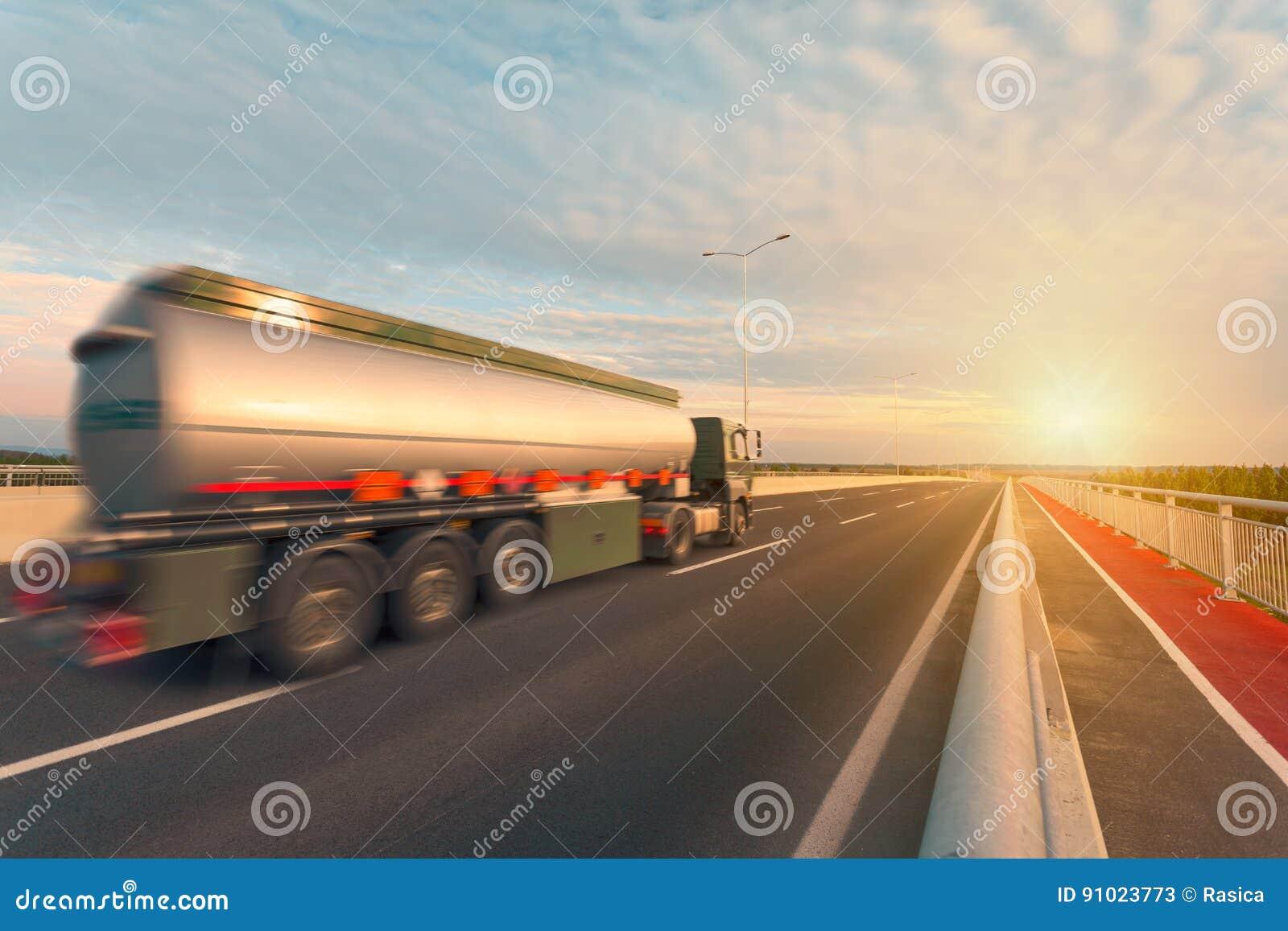 Camión del tanque en la carretera vacía en la puesta del sol