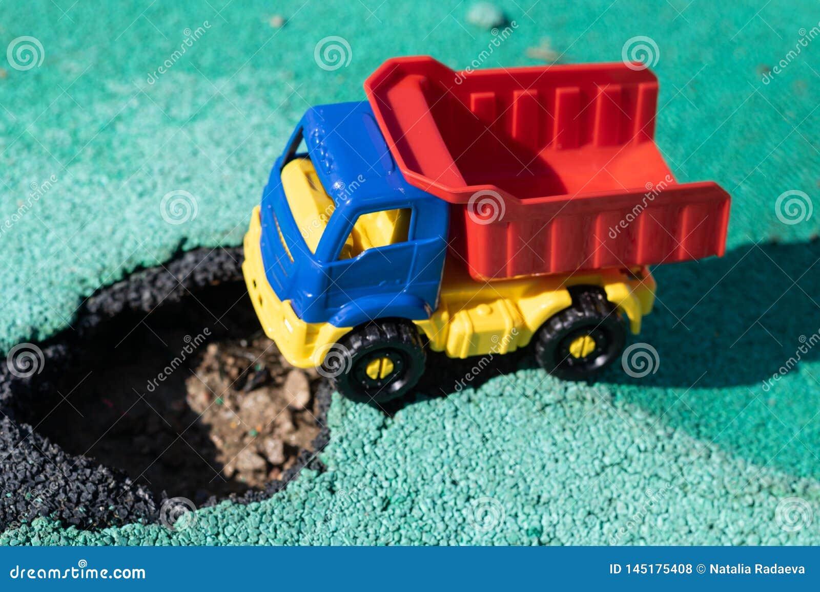 Camión plástico del juguete con un cuerpo rojo parado delante del hoyo El coche no puede ir Agujero en el asfalto El camino nec