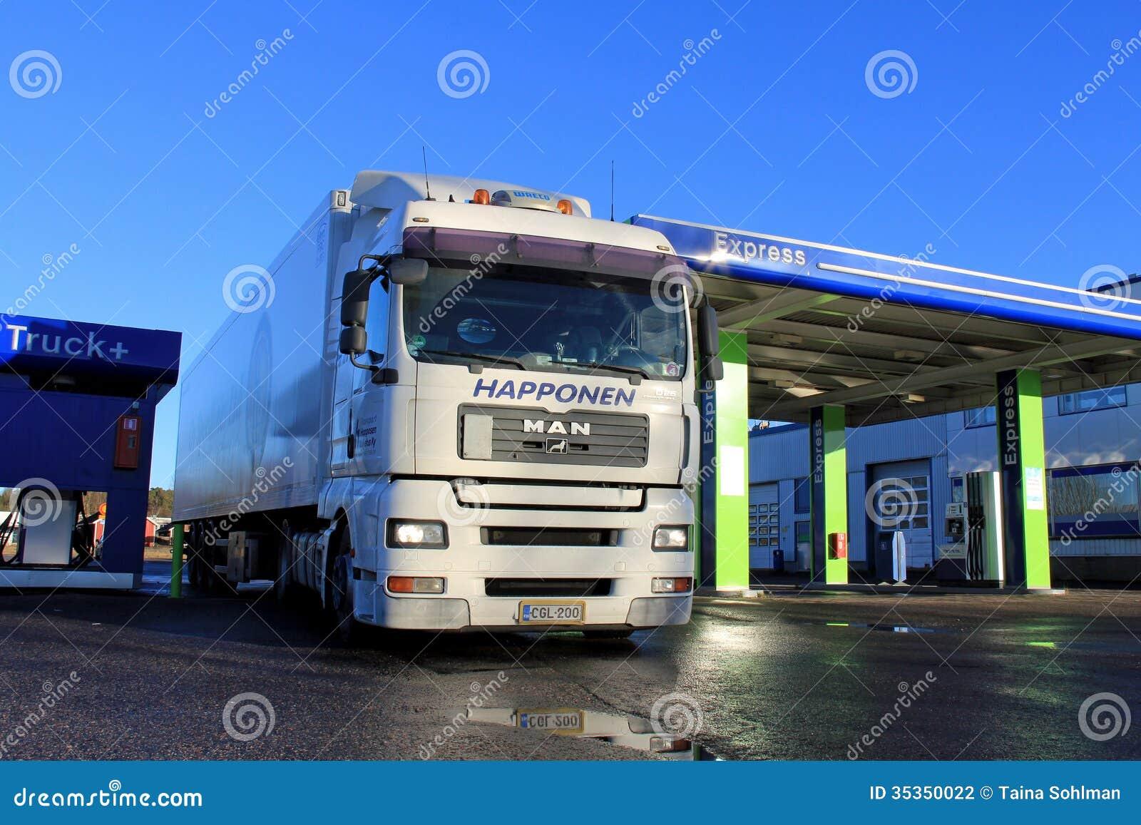 Camión y remolque del hombre blanco 18,480 en una estación de servicio