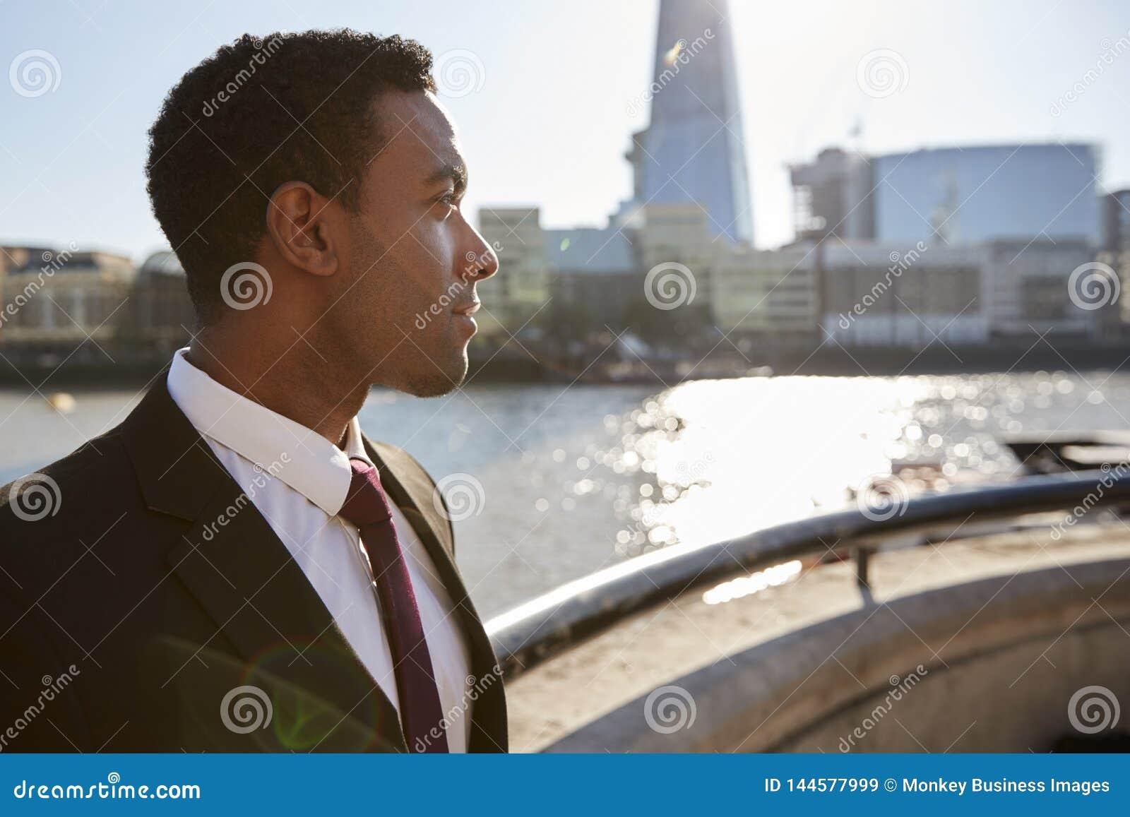 Camicia d uso e legame del giovane uomo d affari nero che fanno una pausa il Tamigi, Londra, distogliere lo sguardo, retroillumin