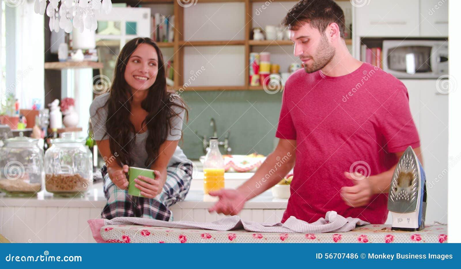 Camicia rivestente di ferro di sorveglianza dell'uomo della donna in cucina archivi video