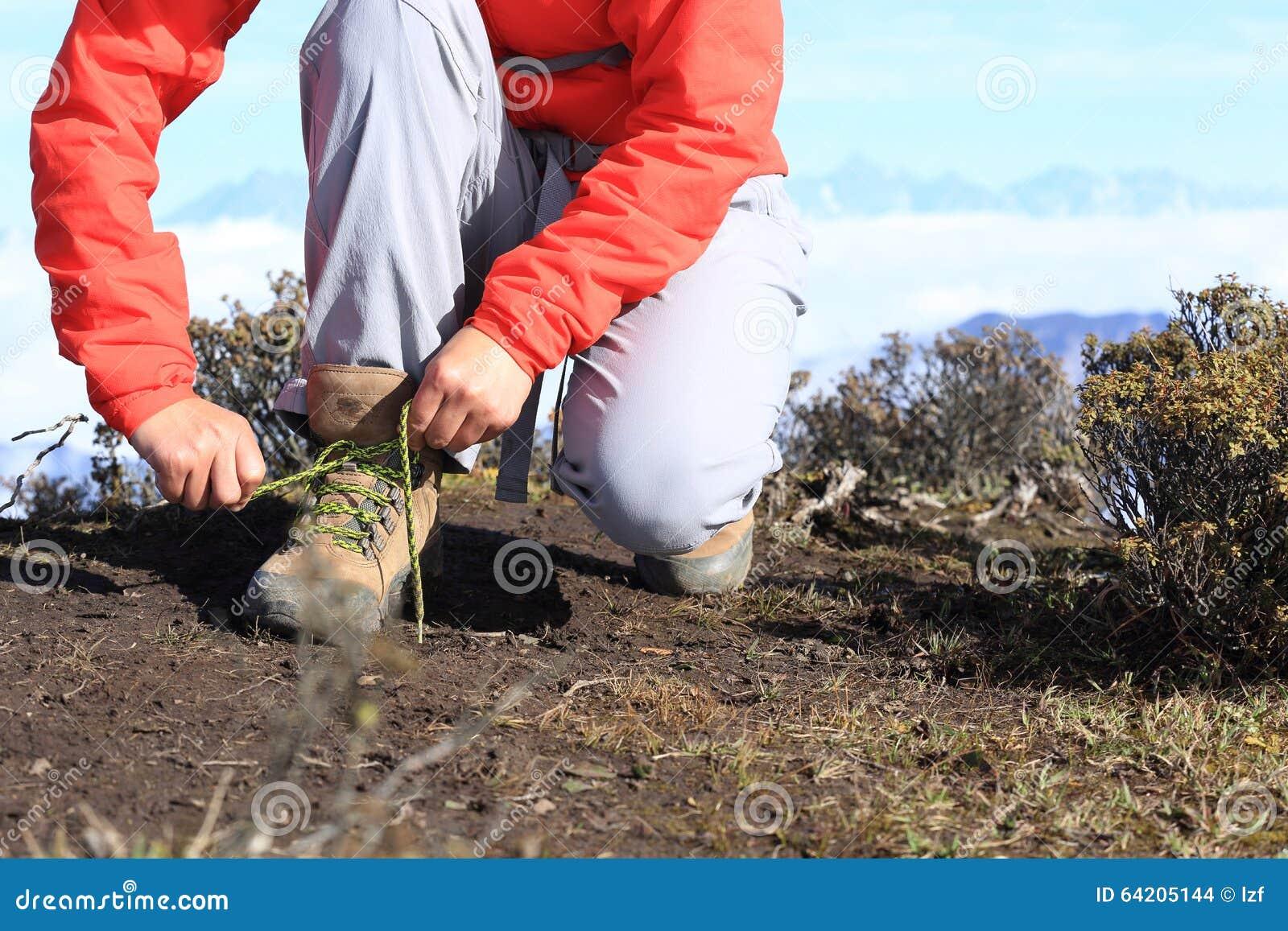 Caminante de la mujer que ata el cordón de caminar botas en pico de montaña