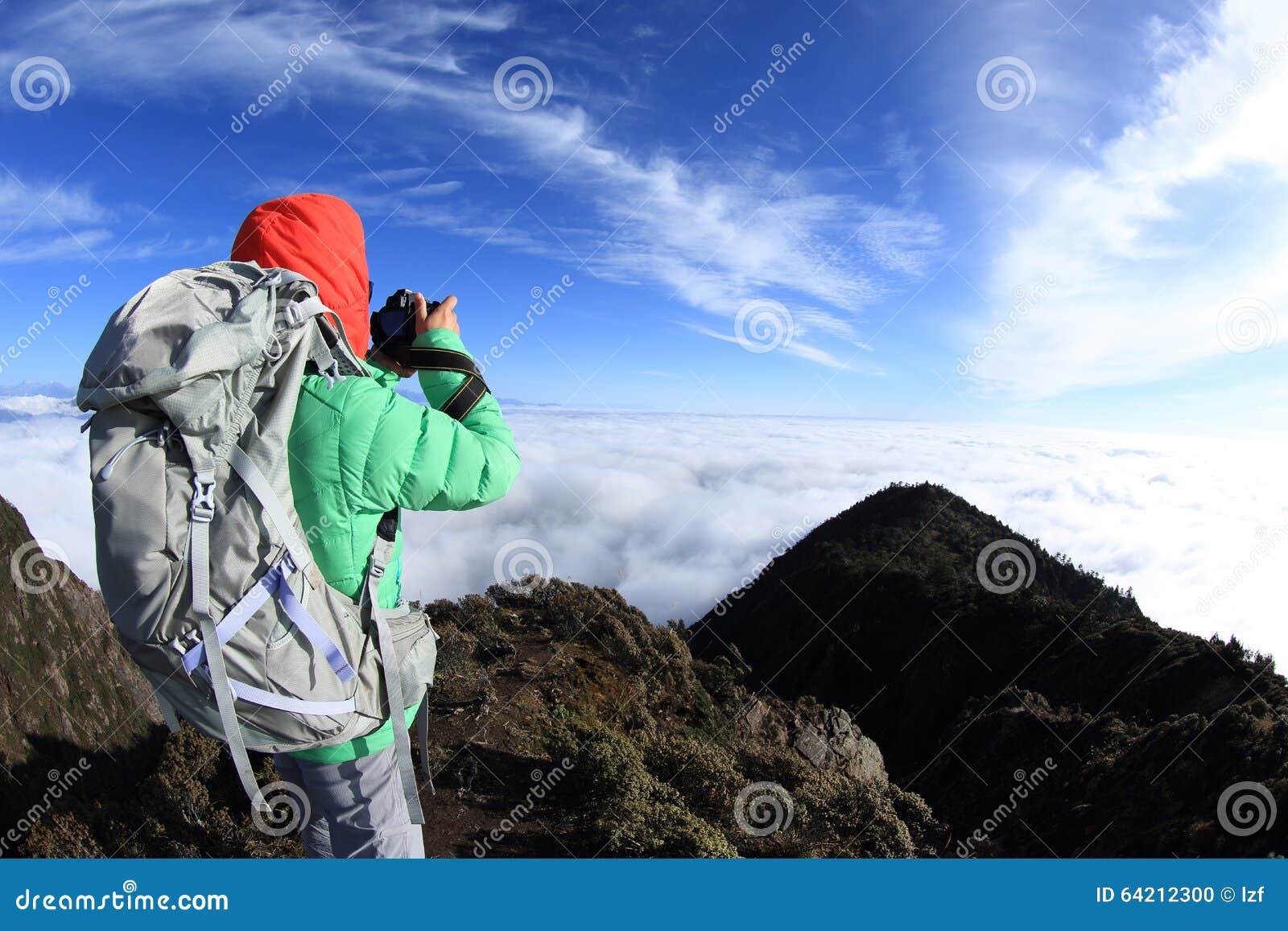 Caminante de la mujer que toma la foto en pico de montaña