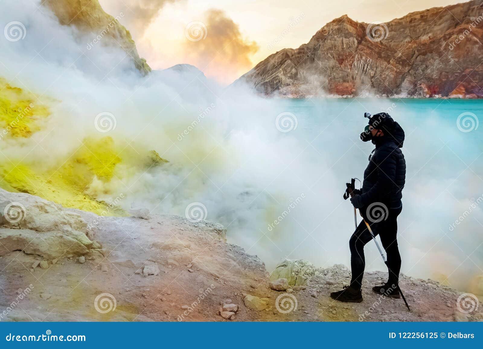 Caminante en el cráter de un volcán Rocas del azufre, lago ácido azul volcánico y humo Un viaje peligroso en el cráter de un acto