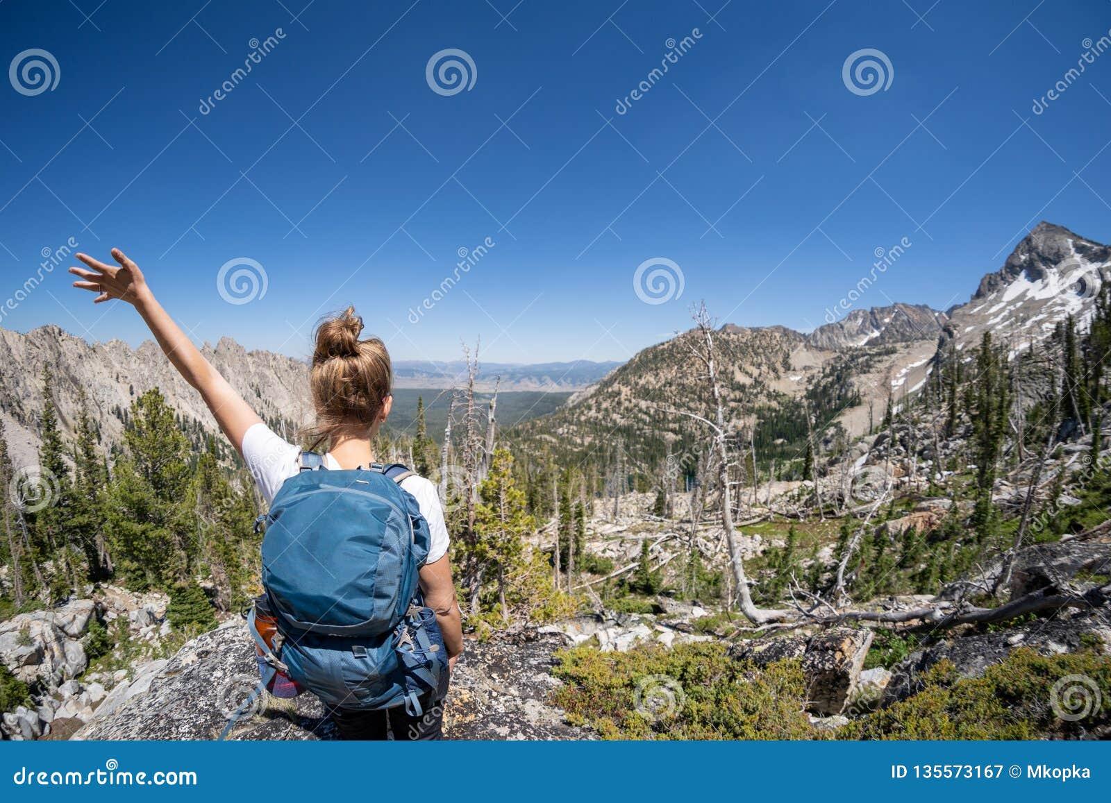 Caminante femenino con la mochila a lo largo del rastro del lago sawtooth en Idaho Cámara trasera del revestimiento Concepto para