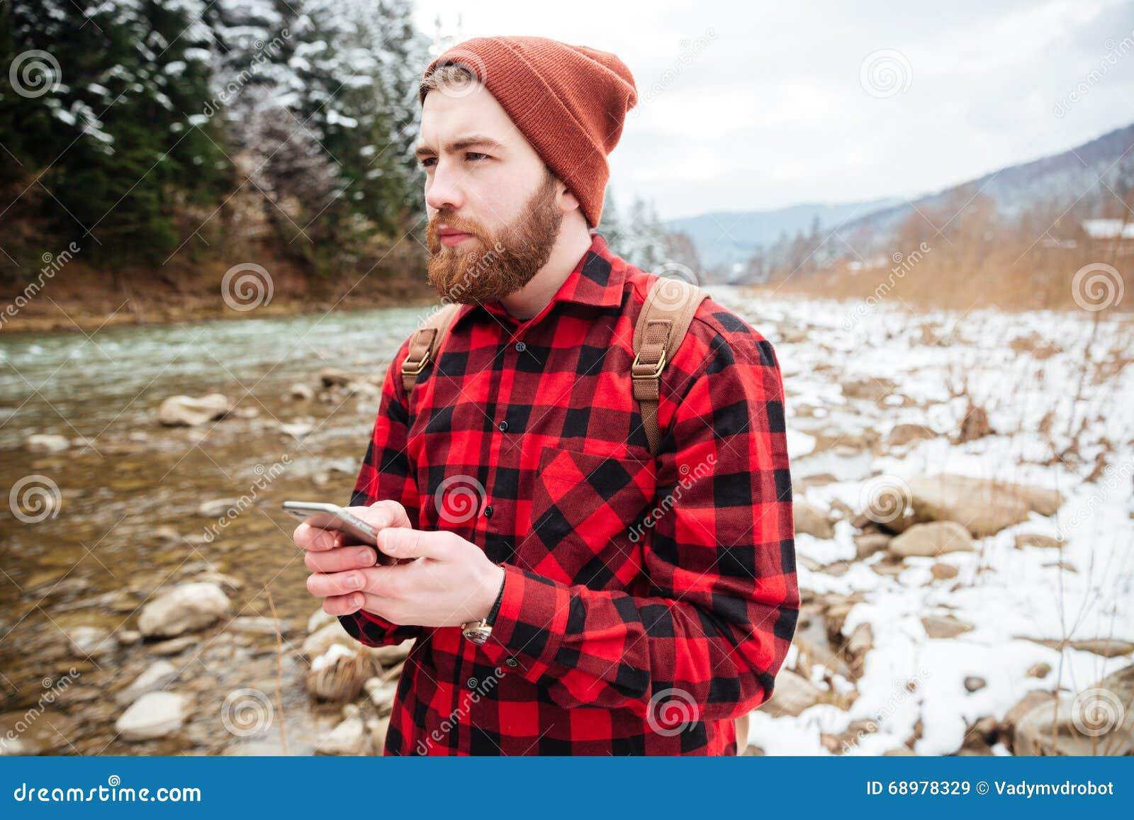Caminante masculino pensativo que sostiene smartphone