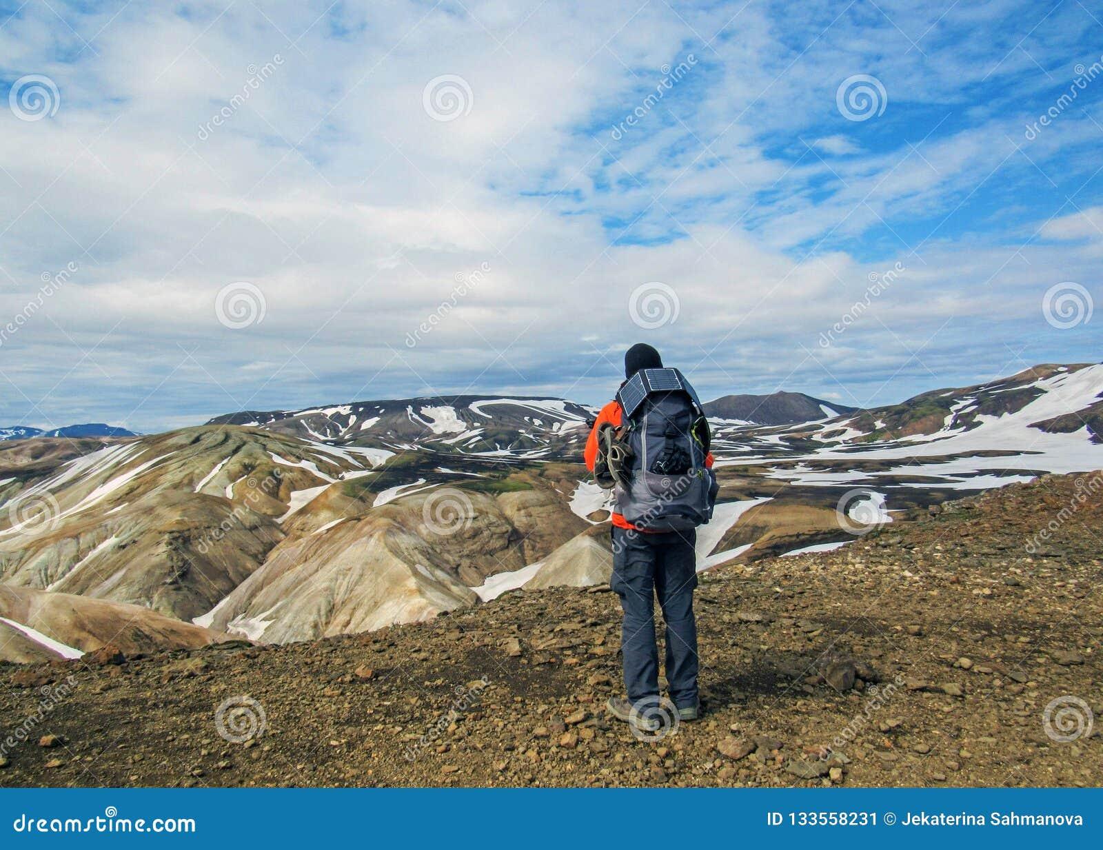 Caminante masculino que camina solamente en el paisaje volcánico de admiración salvaje con la mochila pesada Pasión por los viaje