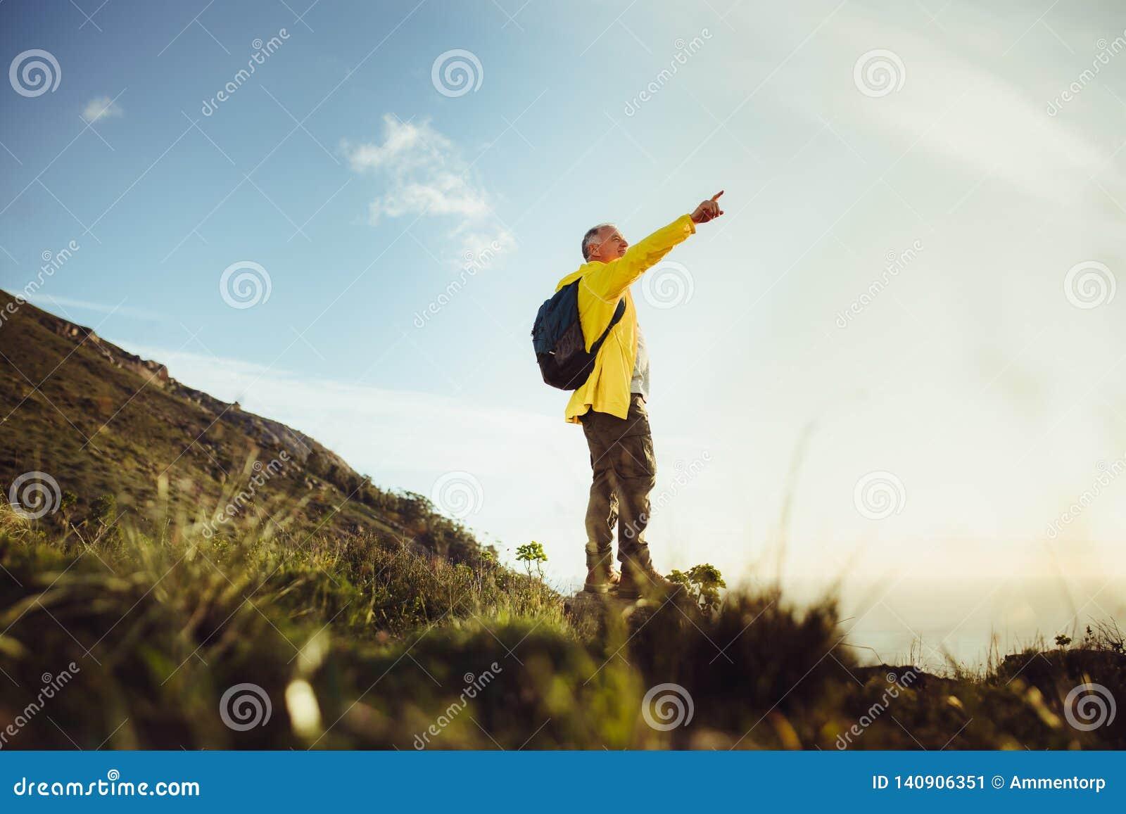Caminante que disfruta de la situación de la visión en una colina