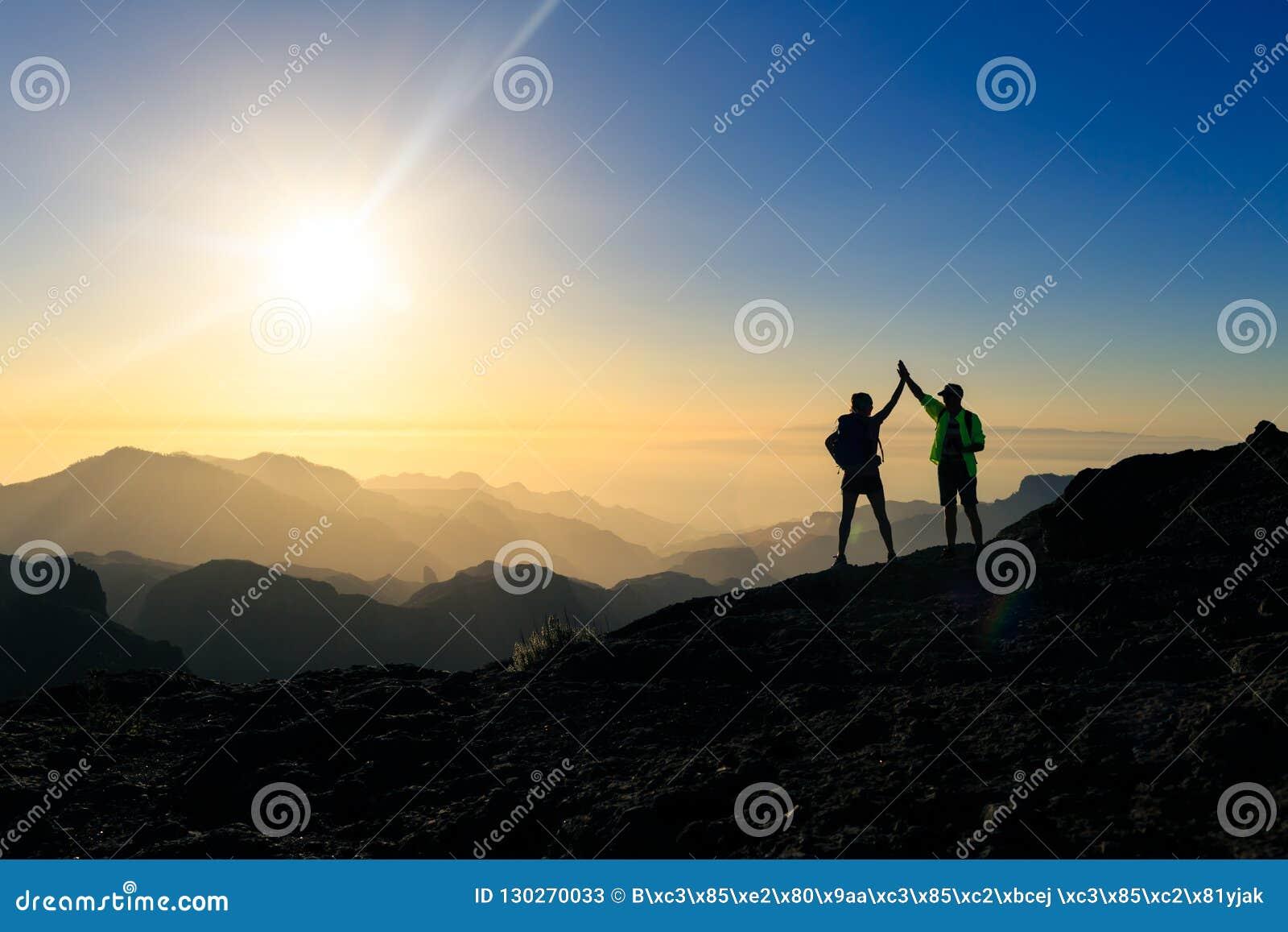 Caminantes de los pares que celebran concepto del éxito en montañas
