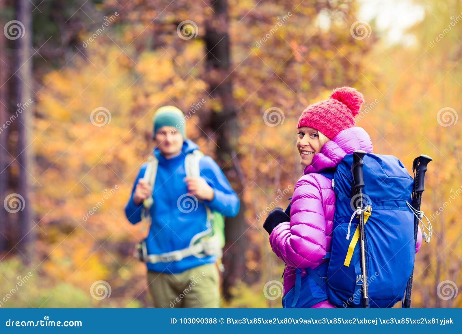 Caminantes felices de los pares del hombre y de la mujer que acampan en bosque del otoño