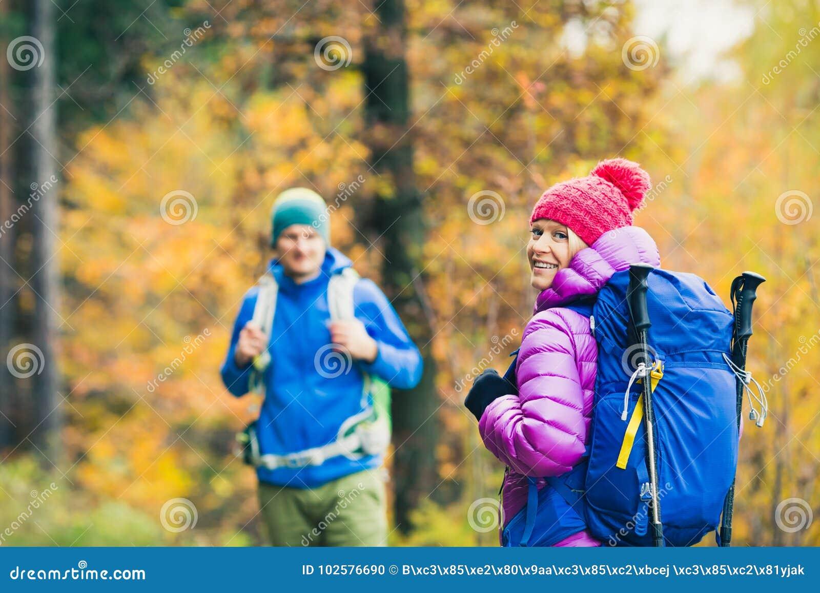 Caminantes felices de los pares del hombre y de la mujer que caminan en bosque del otoño