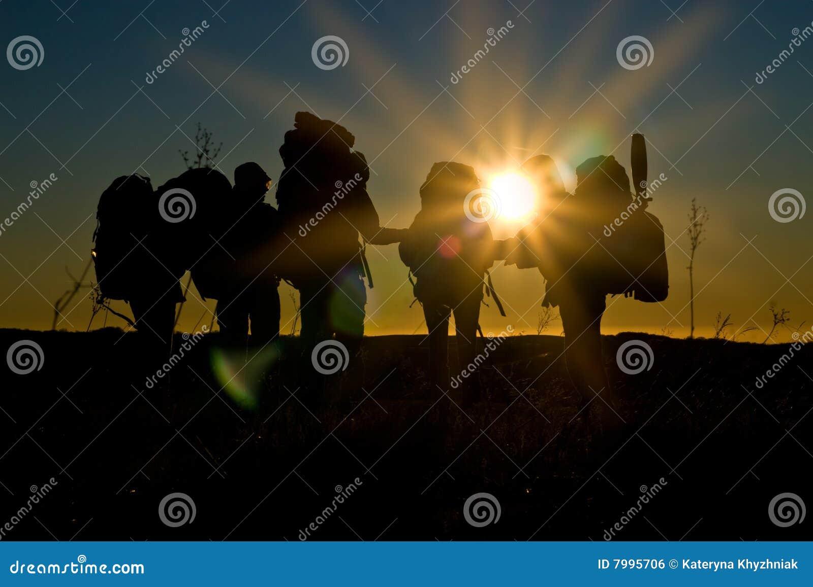 Caminata de los caminantes en puesta del sol con los rayos de sol