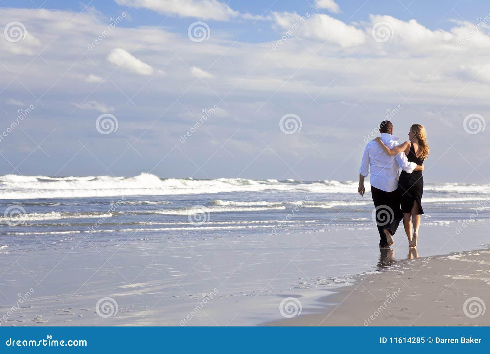 Caminata romántica de los pares del hombre y de la mujer en una playa