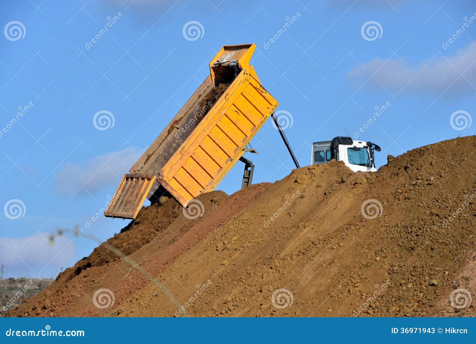 Caminhão basculante que descarrega o solo durante trabalhos de estrada