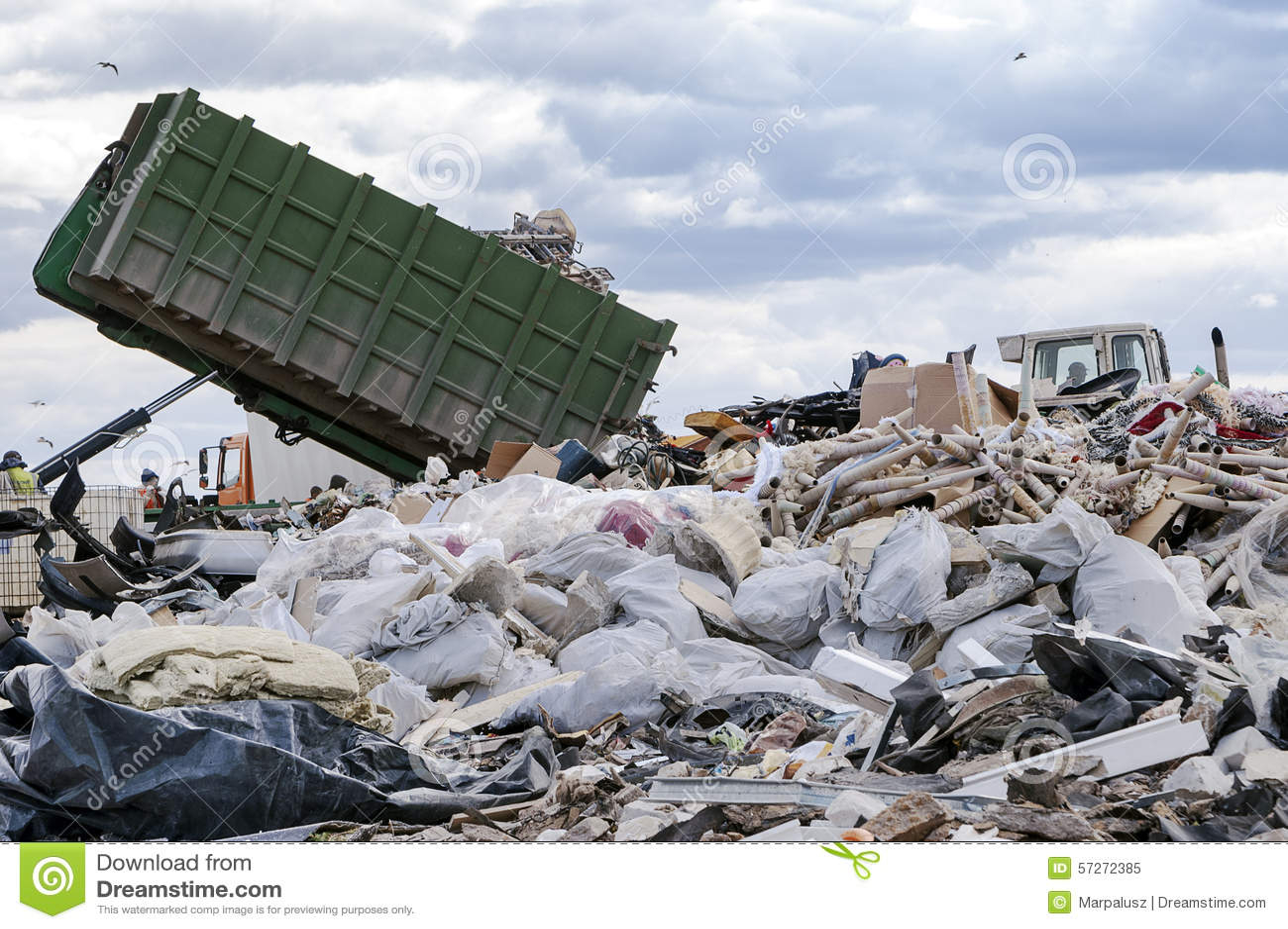 Caminhão de lixo que descarrega o lixo na terra de despejo