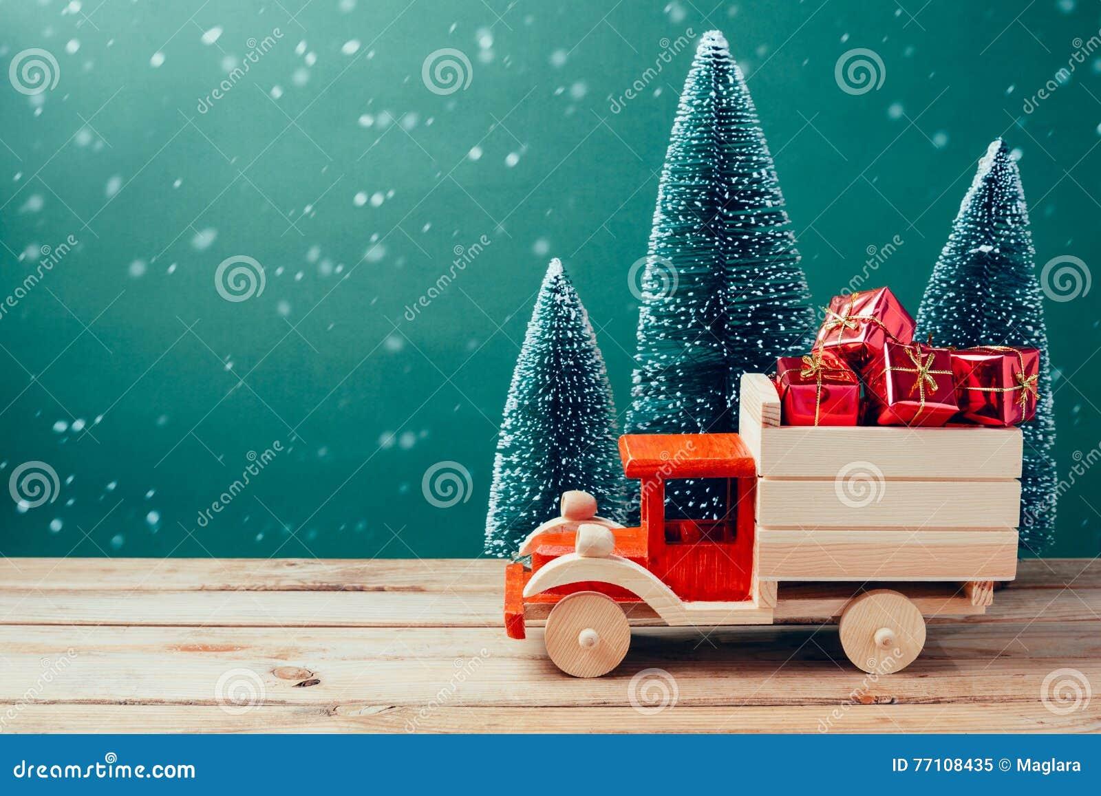 Caminhão do brinquedo do Natal com caixas de presente e pinheiro na tabela de madeira sobre o fundo verde