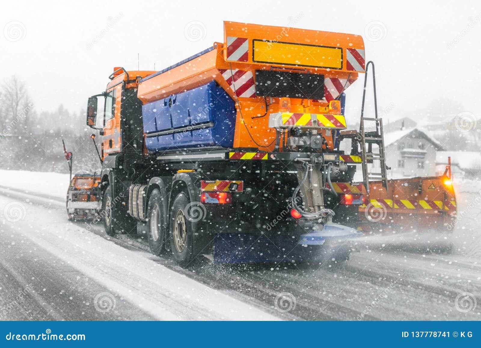Caminhão do Snowplow que remove a neve suja da rua ou da estrada da cidade durante quedas de neve pesadas Situação da estrada do