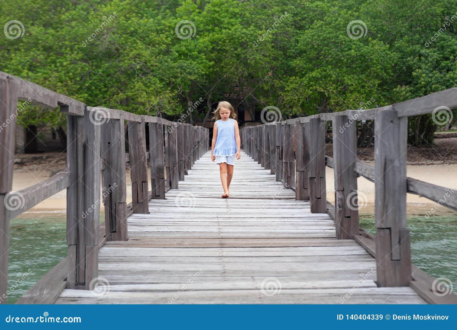 Caminhada da moça pelo cais de madeira na praia da areia do mar