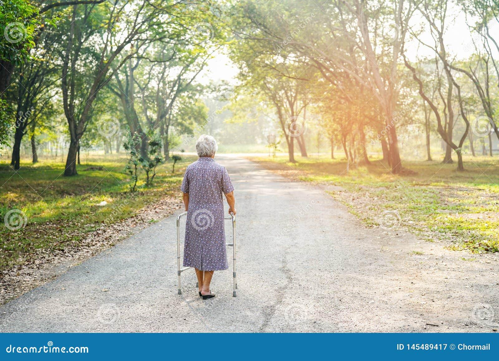 Caminhada paciente asi?tica da mulher superior ou idosa da senhora idosa com o caminhante no parque