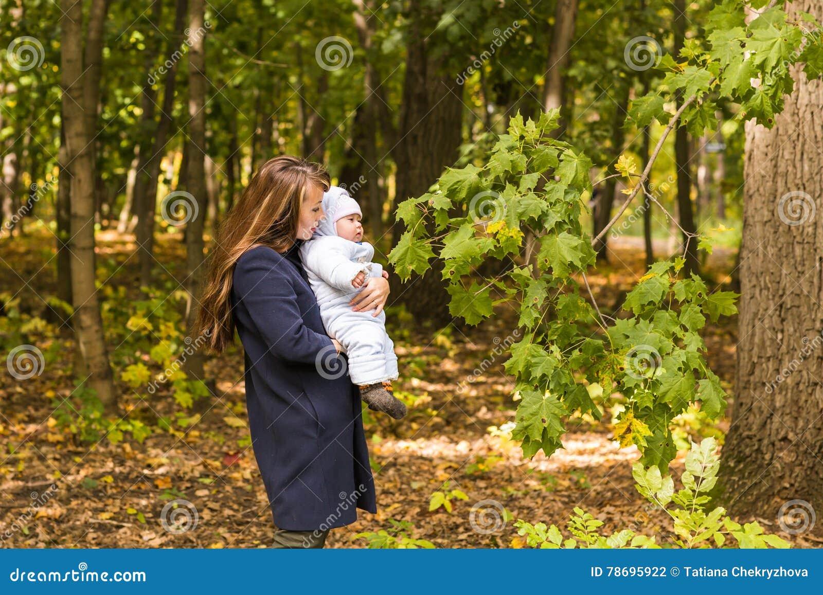 Caminhadas bonitas no parque, luz solar morna da mãe e da criança da foto do outono do estilo de vida