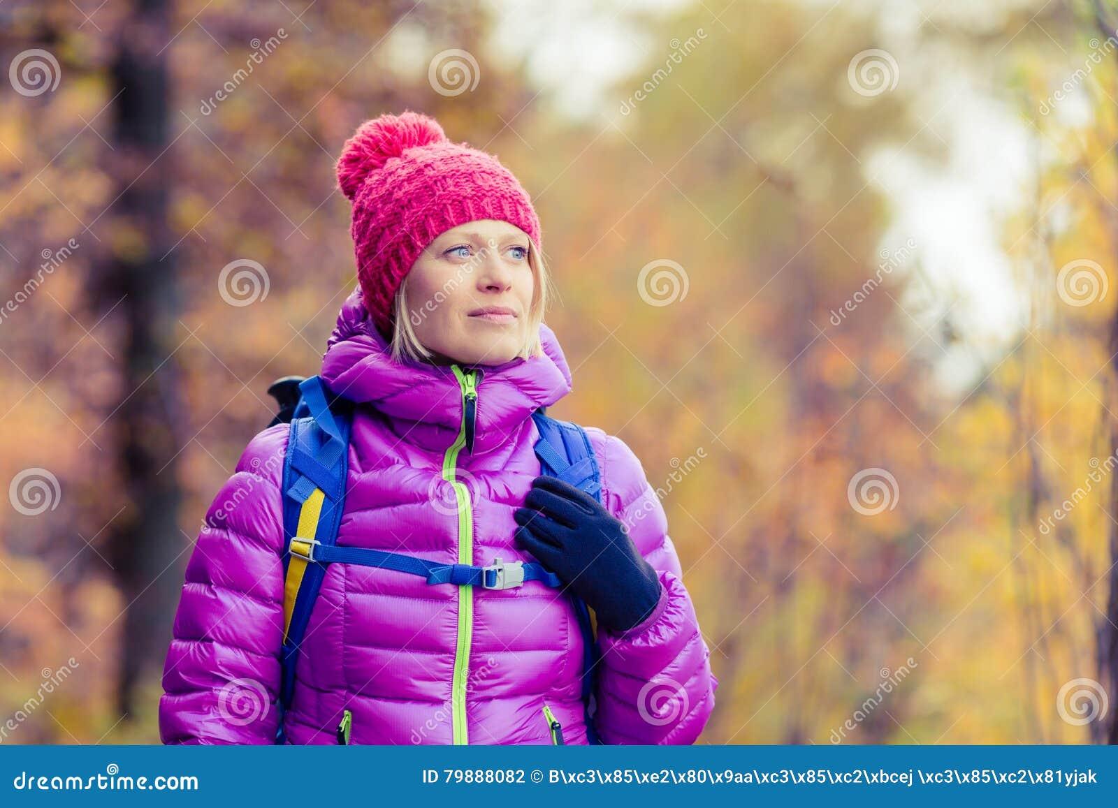 Caminhando a mulher com a trouxa que olha a câmera no au inspirado